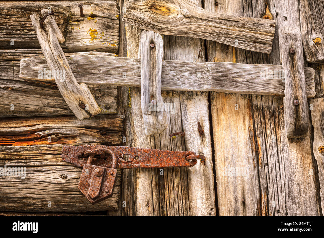 An old wooden log door is closed locked and latched with a log beam and a rusty pick lock in cast iron. & An old wooden log door is closed locked and latched with a log beam ...