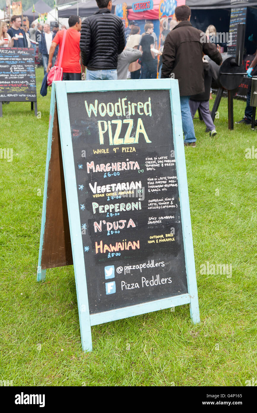 Woodfired Pizza Sign_Food stall vans at the Afric Oye festival in Sefton Park, Liverpool, Merseyside, UK - Stock Image