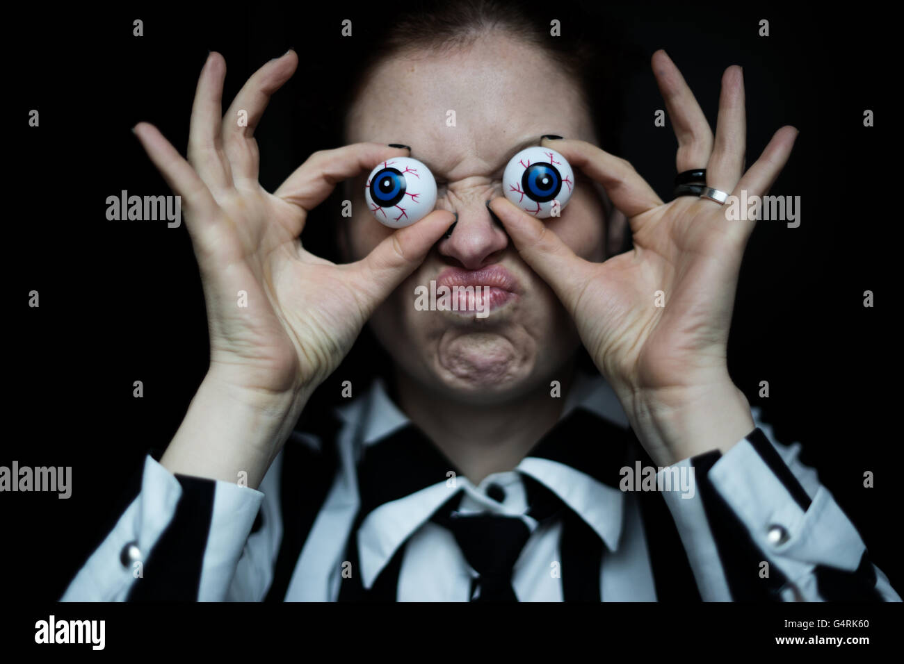 Woman grimacing, artificial eyes - Stock Image