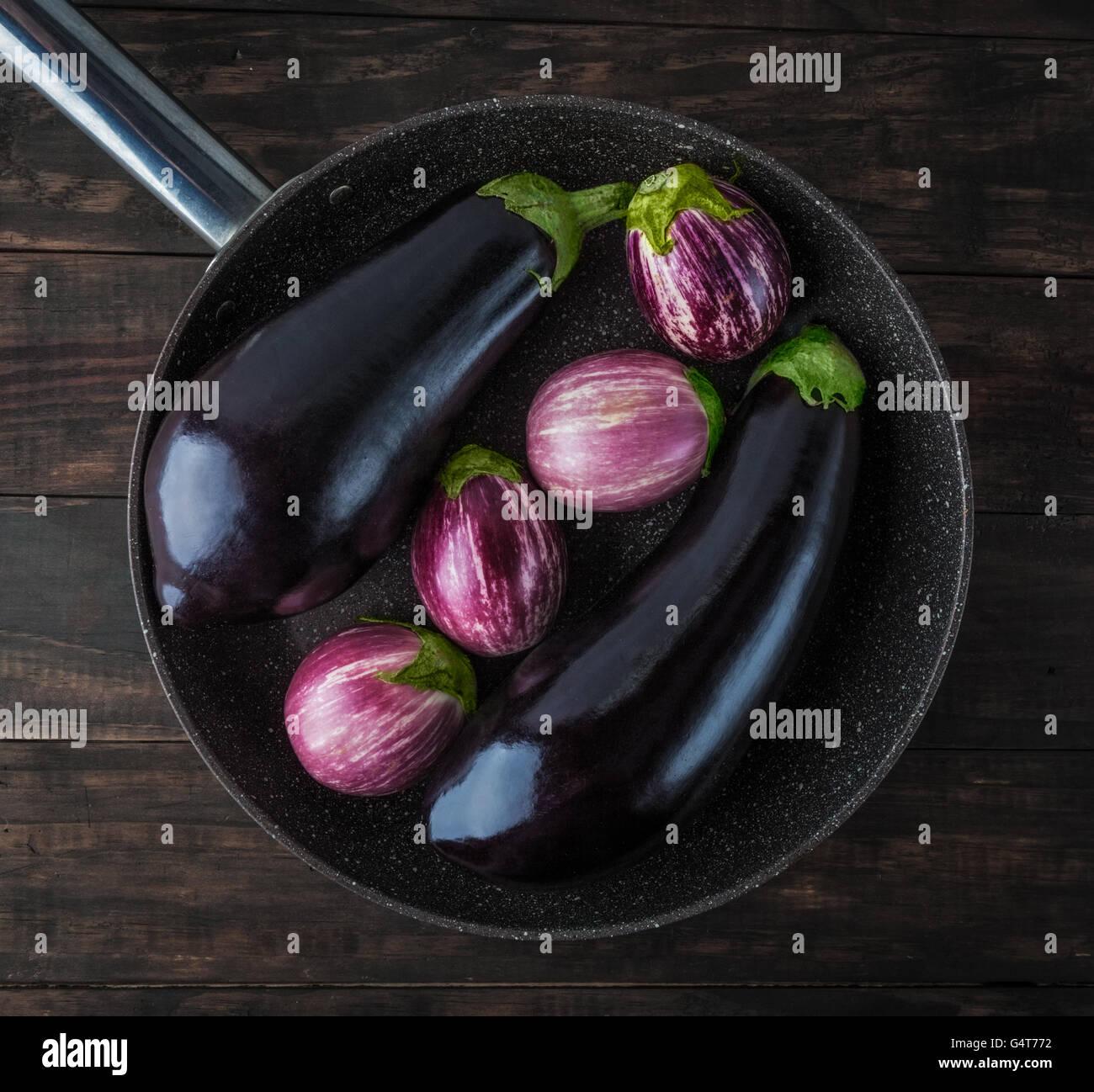Whole eggplants on frying pan top view. Classic and Listada de Gandia varieties. Top view. - Stock Image