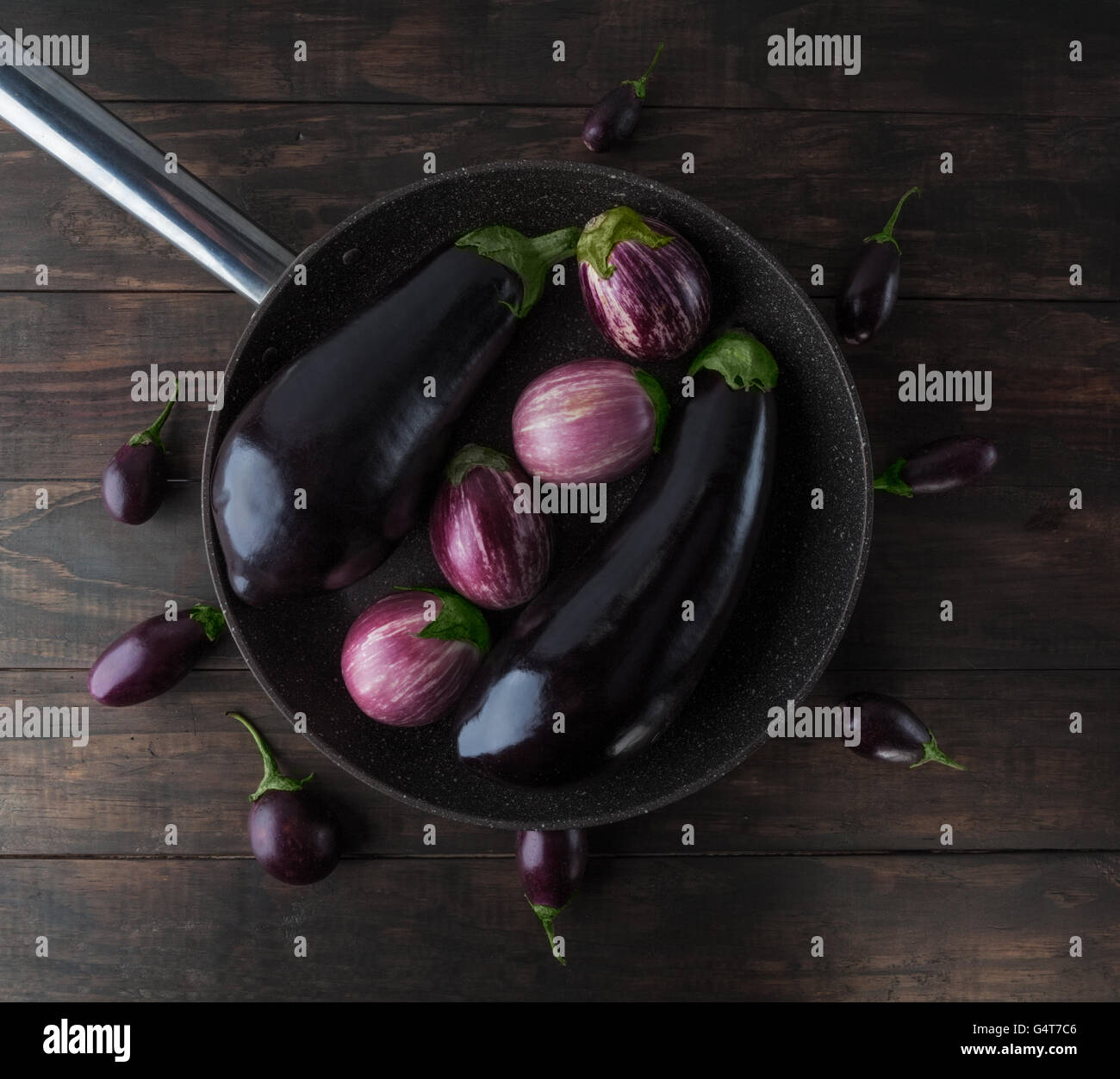 Eggplants arranged on frying pan placed on wooden table. Top view. - Stock Image