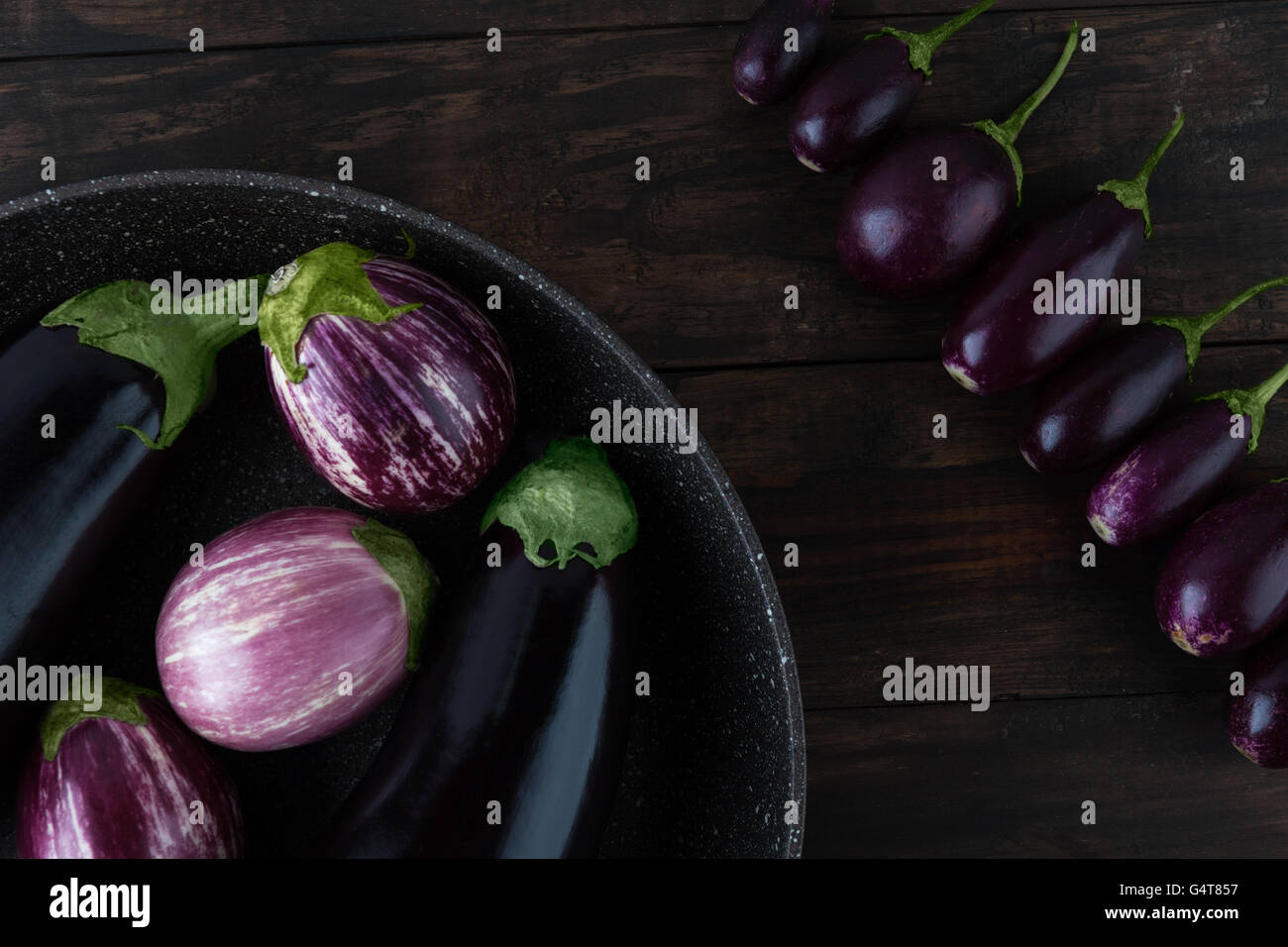 Eggplant varieties arranged creatively on frying pan and wooden table closeup. Top view. - Stock Image