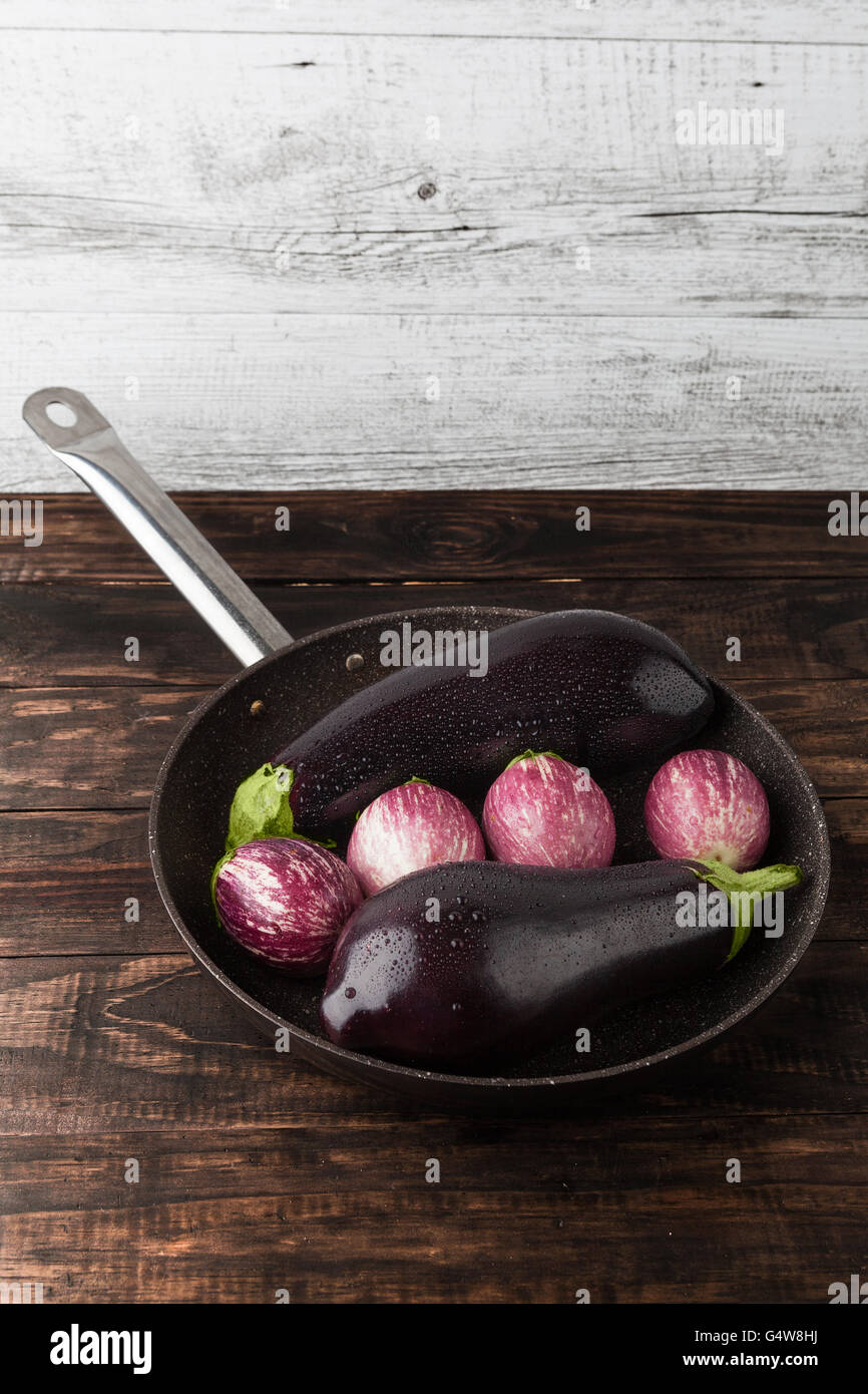 Wet eggplants in frying pan on rustic wooden table. Vertical image with copy space - Stock Image
