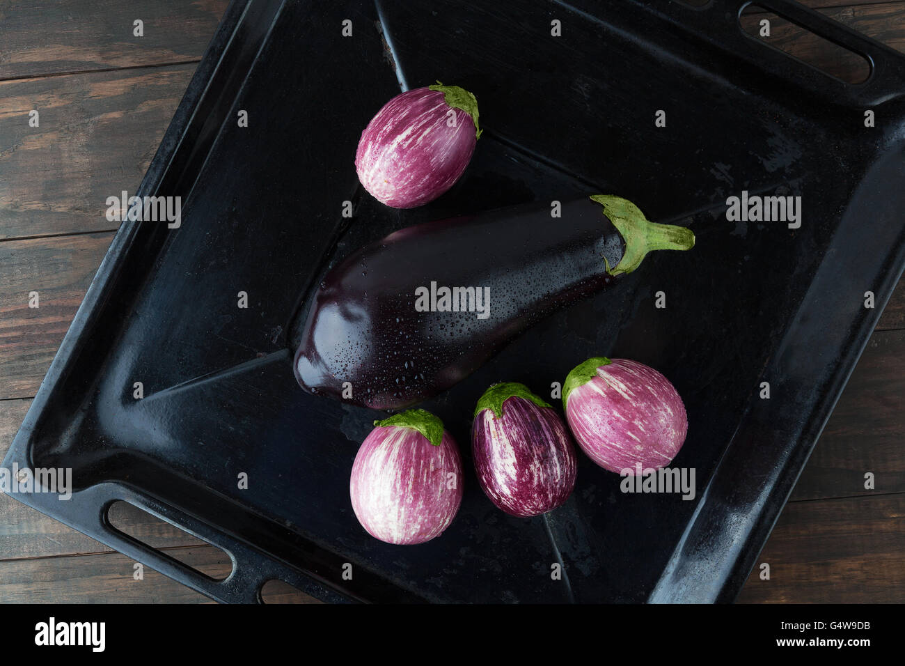 Wet eggplants - black magic, and purple striped eggplants in rustic baking tray. Top view with copy space - Stock Image