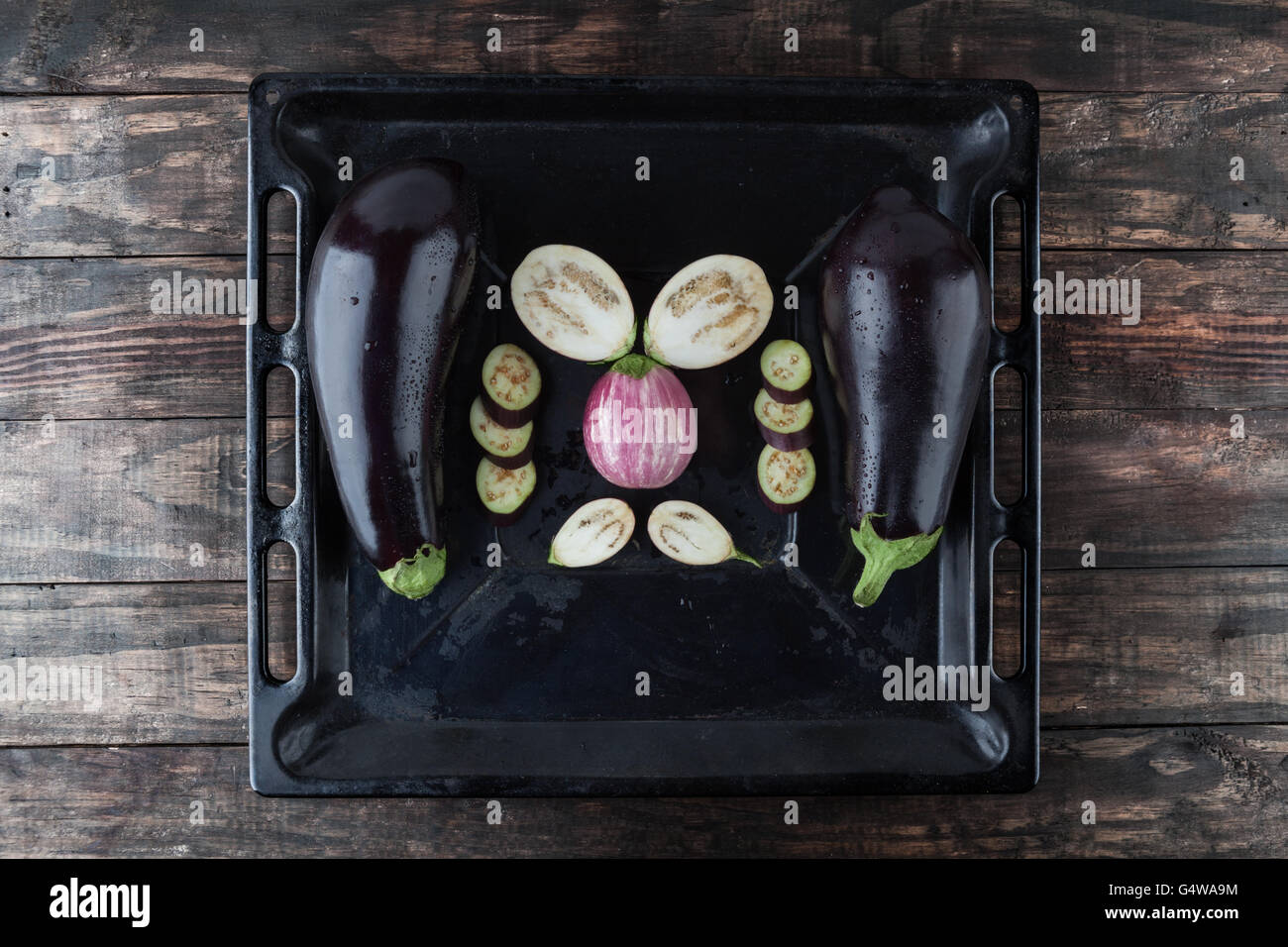 Whole and sliced eggplants arranged on rustic baking tray. Top view with copy space - Stock Image