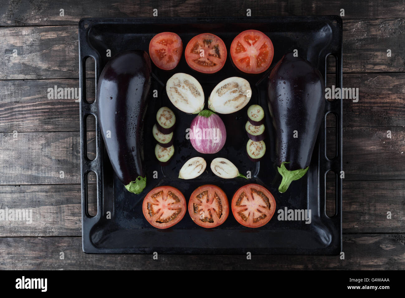 Whole and sliced eggplants and tomatoes on rustic baking tray. Top view. - Stock Image