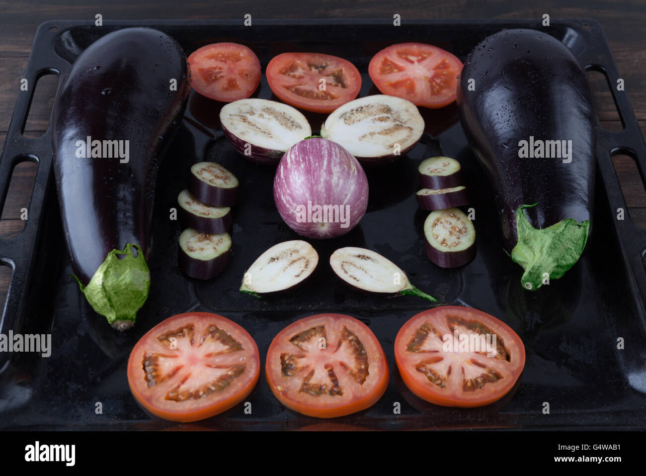 Whole and sliced eggplants and tomatoes on rustic baking tray. Shallow depth of field - Stock Image