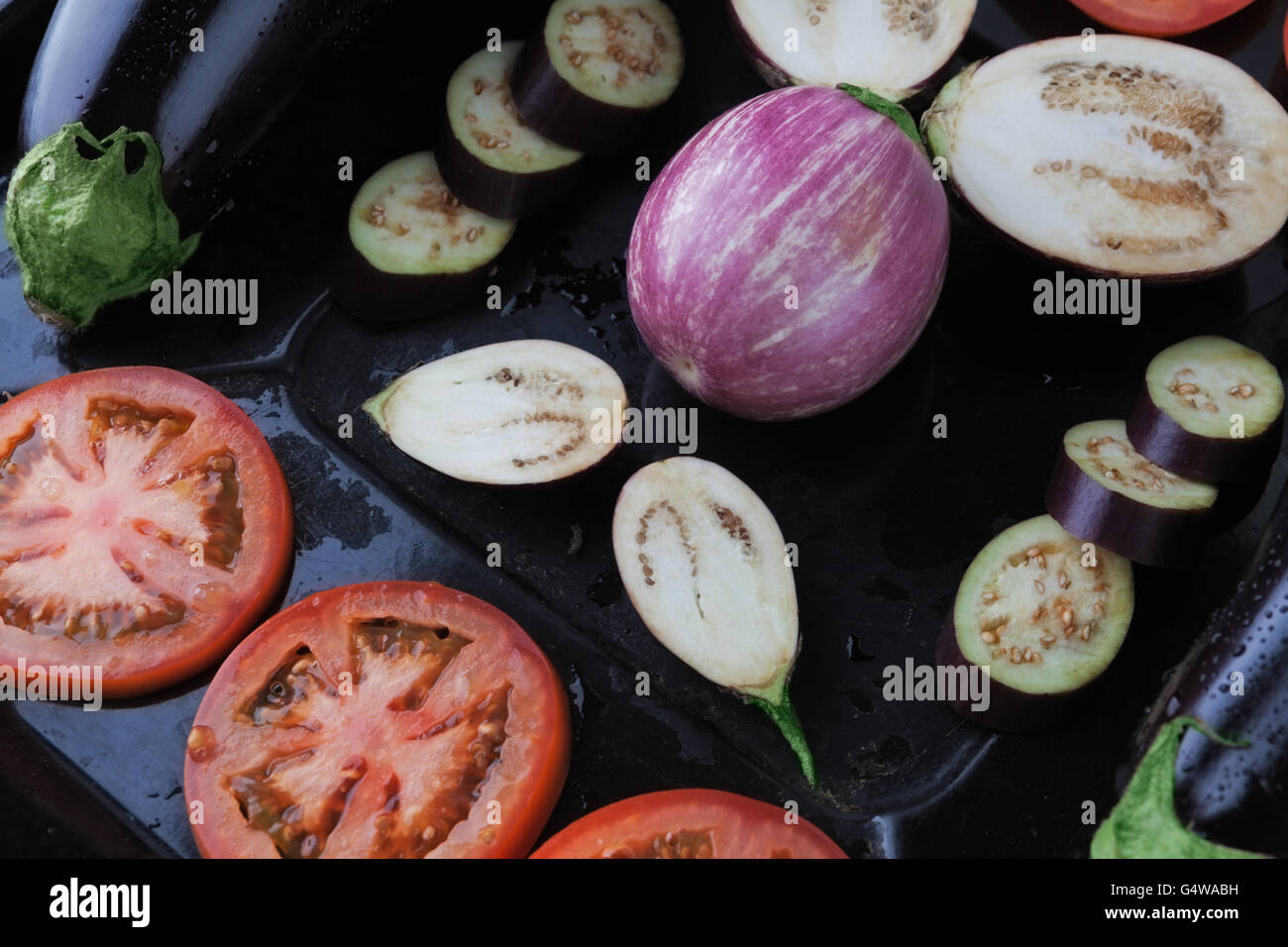 Whole and sliced eggplants and tomatoes on rustic baking tray closeup. Shallow depth of field - Stock Image