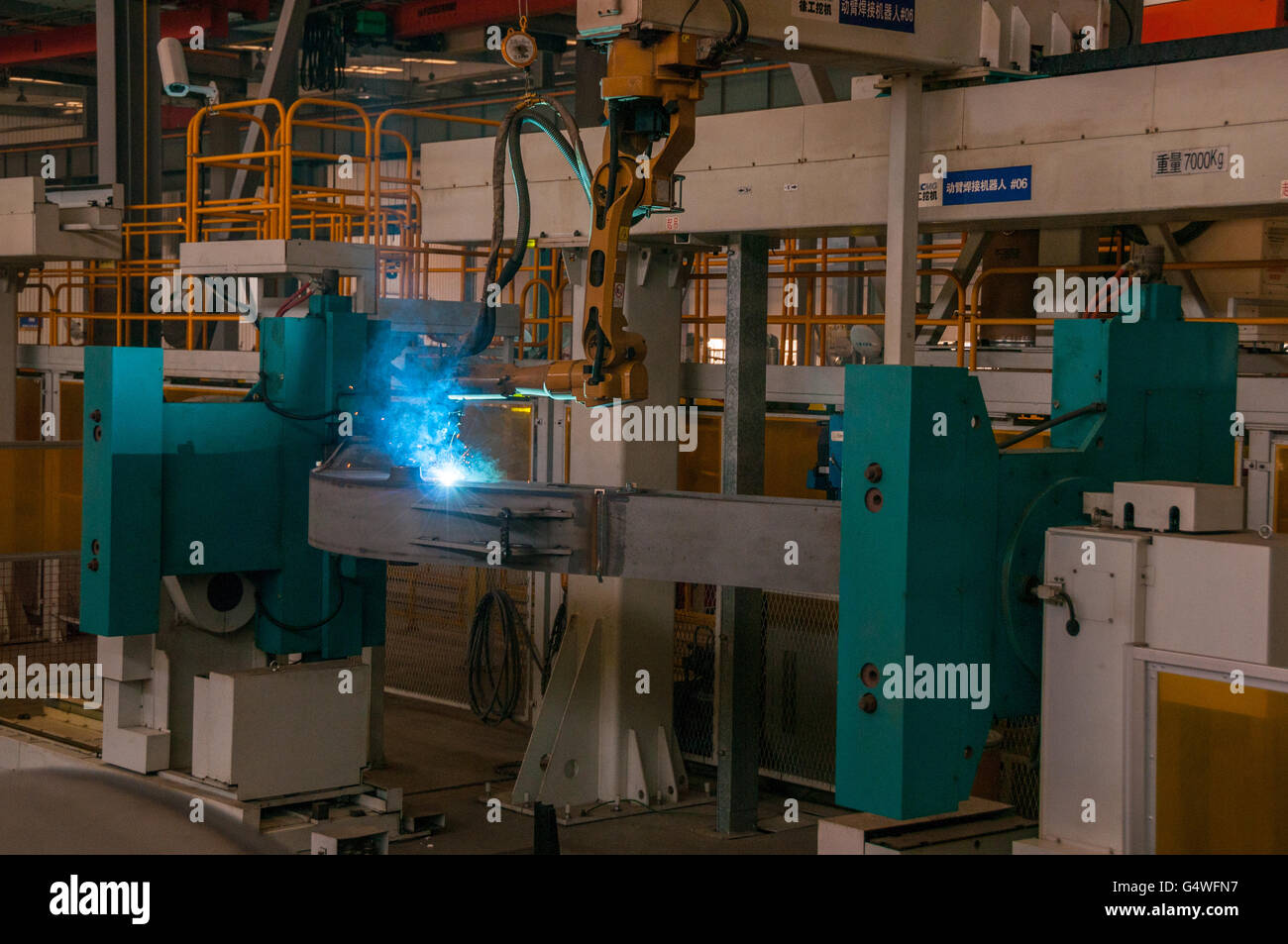 A robot welder in operation working on an excavator boom in the XCMG excavator factory in Xuzhou, China. - Stock Image