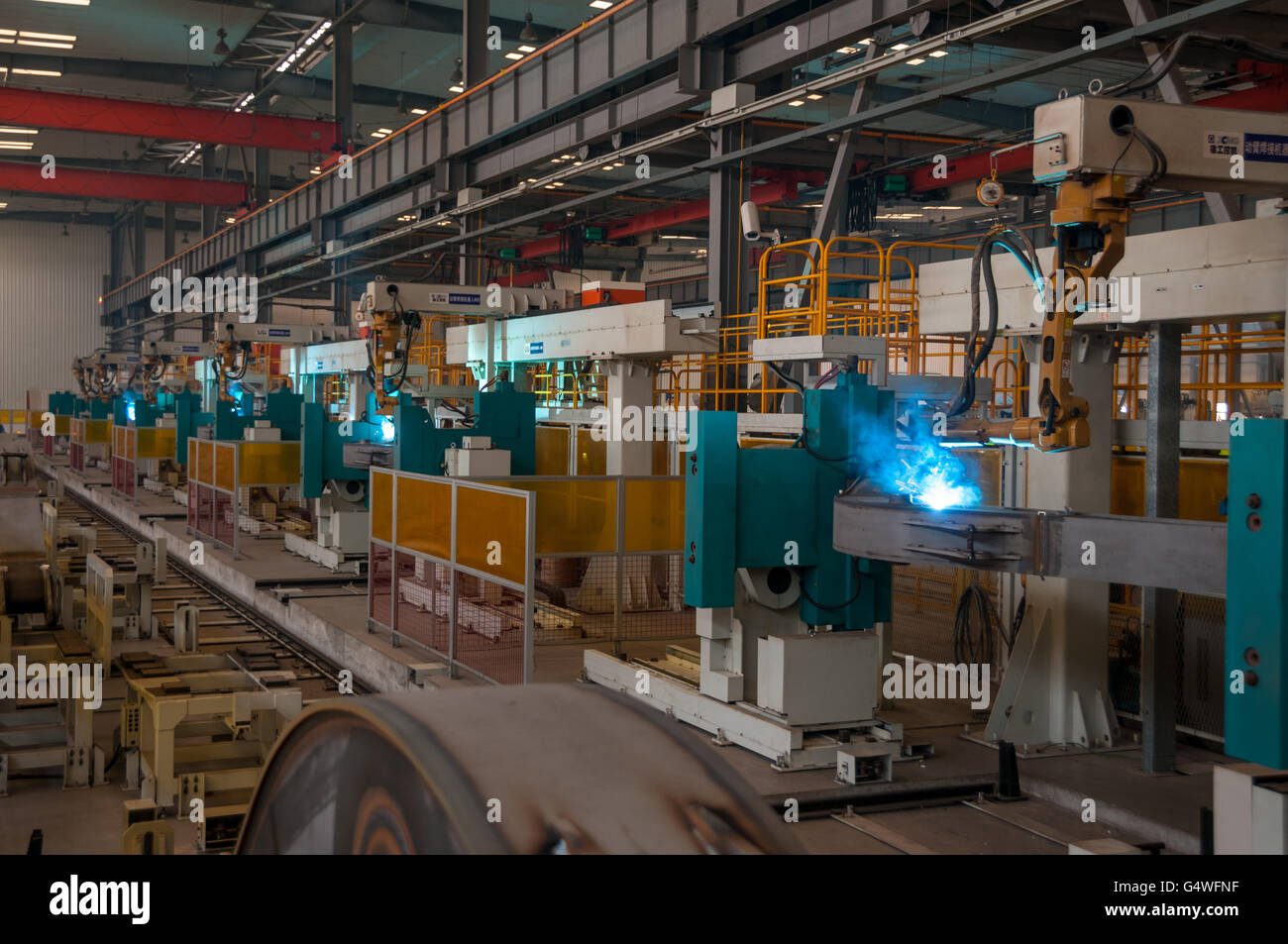 A line or robot welders in operation in the XCMG excavator factory in Xuzhou, China. - Stock Image