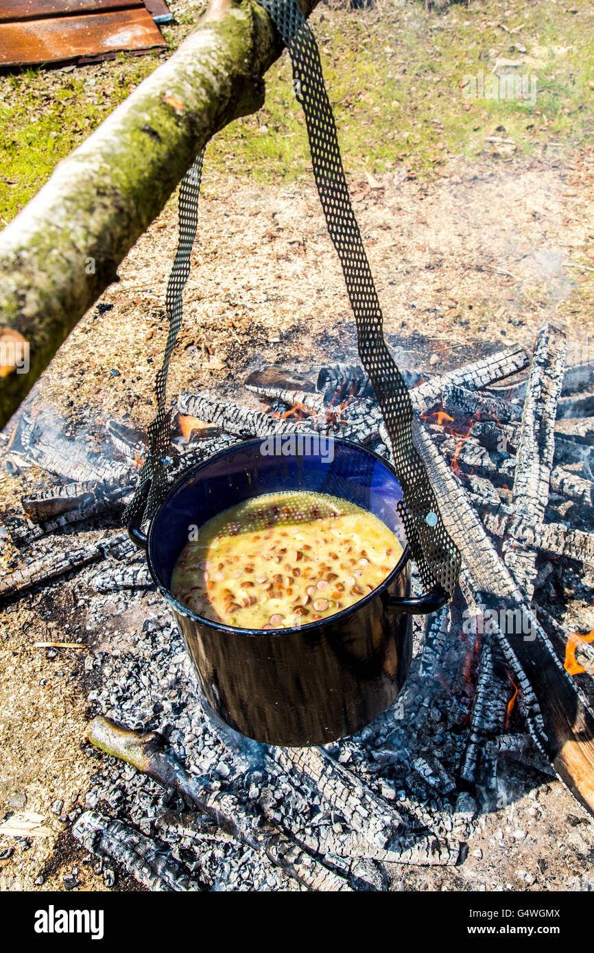Stockpot, cooking over an open campfire, pea soup with sausages, Stock Photo