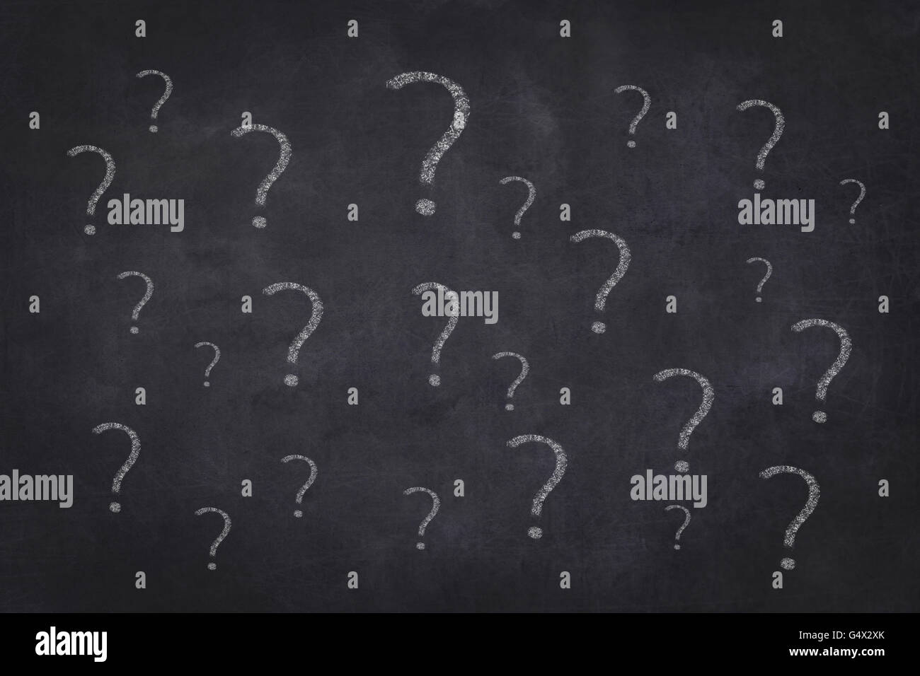many question marks on chalkboard background - Stock Image