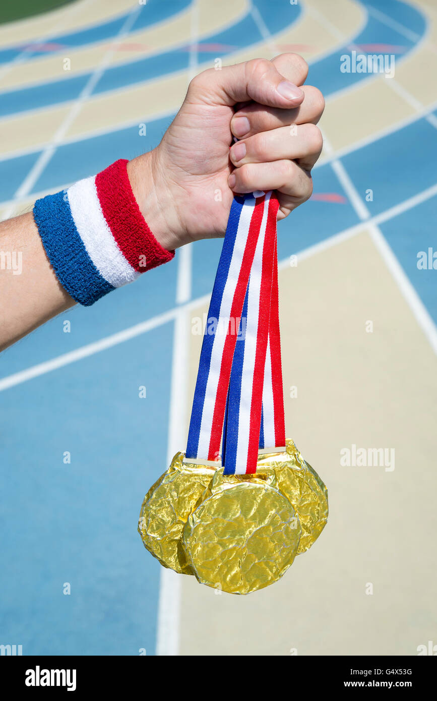 Hand of American athlete holding gold medals hanging from