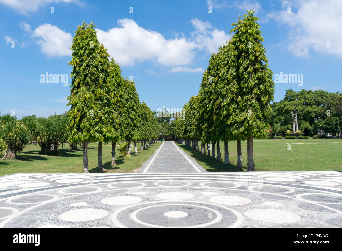Avenue with tall trees leading to Bajra Sandhi Monument in Denpasar, Bali - Stock Image