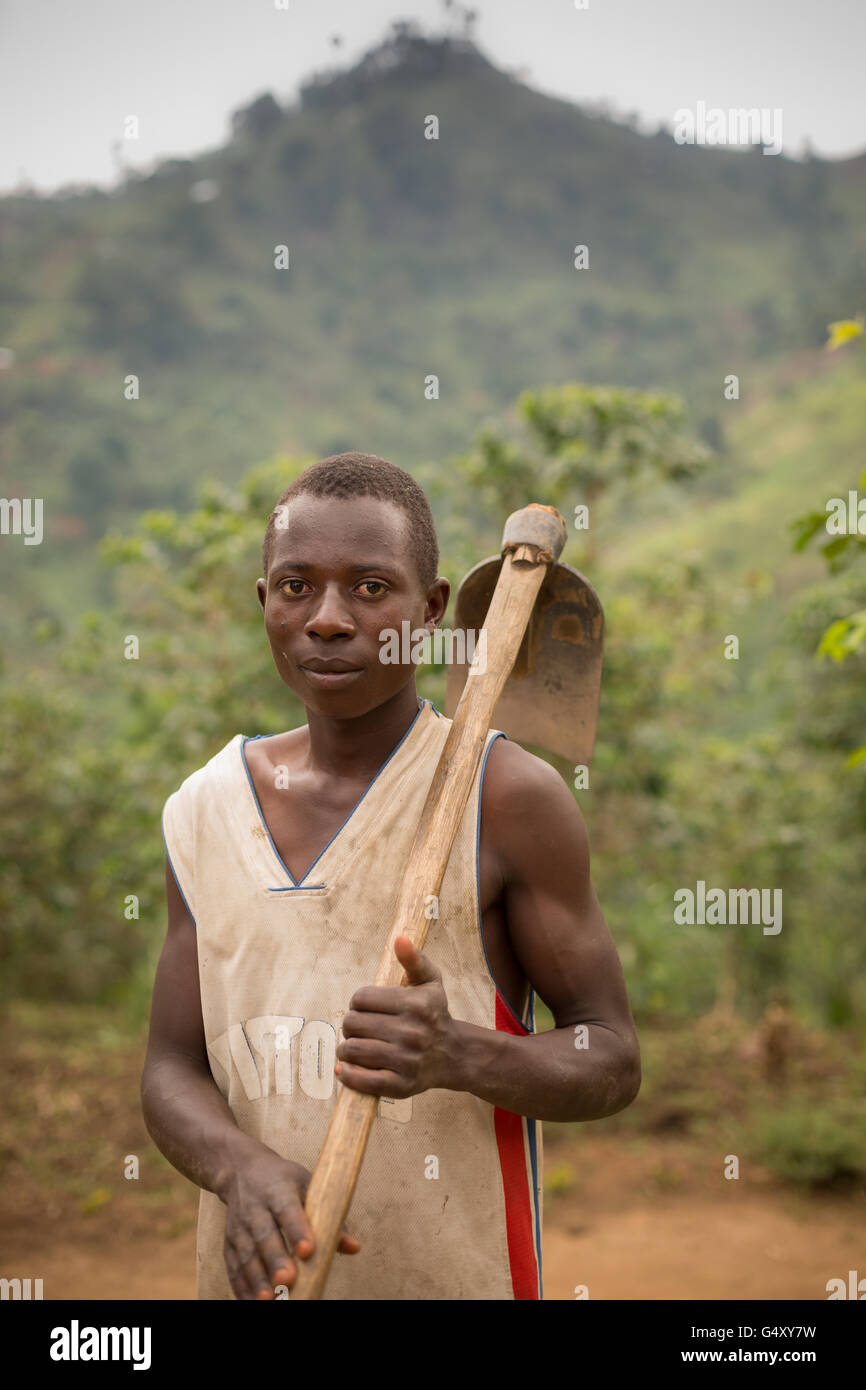 A farmer pauses from working in his field in rural Kasese District, Uganda, East Africa. - Stock Image