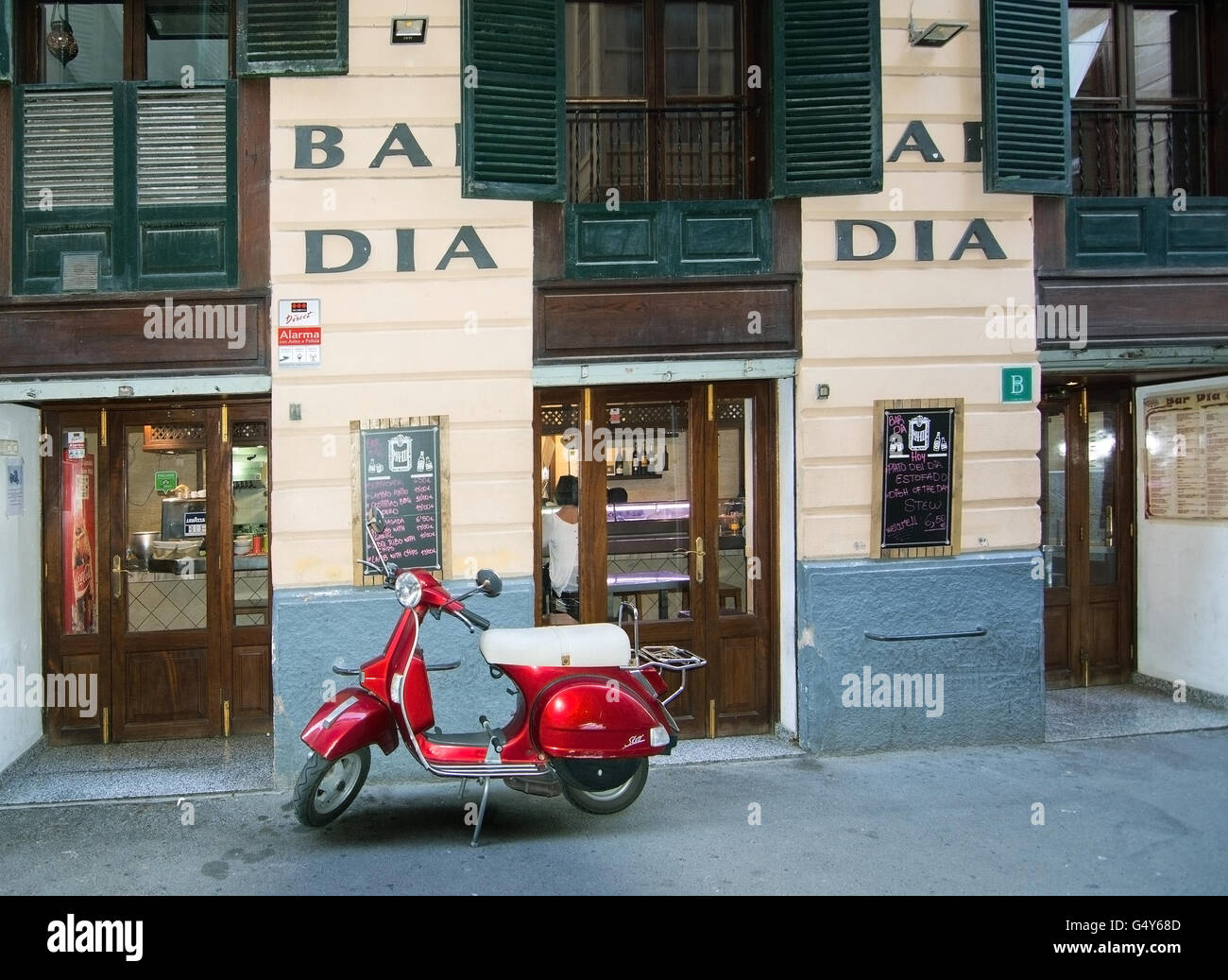 Red vespa scooter parked in front of Bar Dia Restaurant on Carrer des Apuntadores in Palma de Mallorca, Balearic - Stock Image