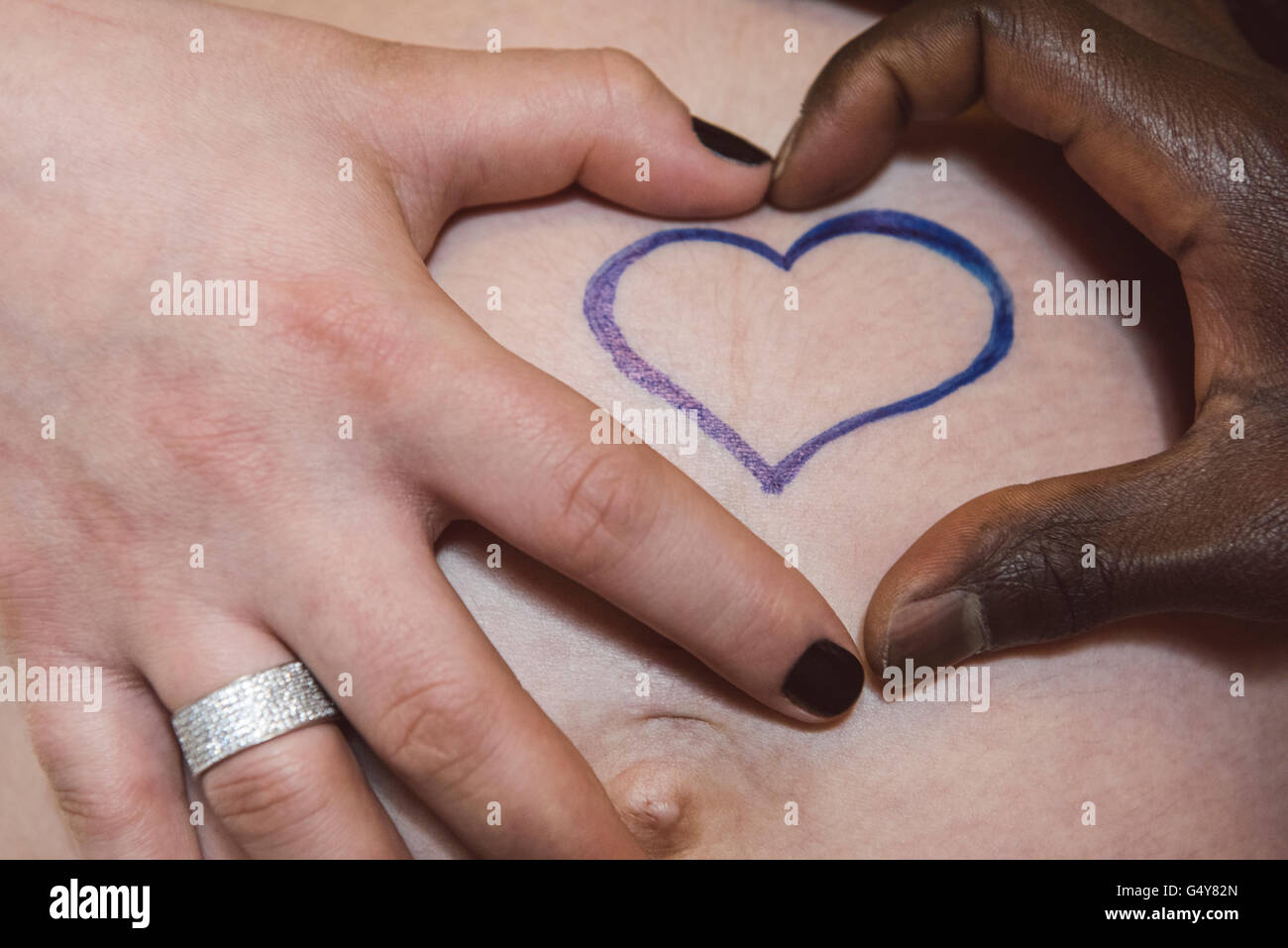 Heart shaped hands of a pregnant woman and her partner over tummy ...