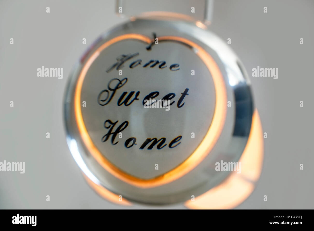 Crystal ball showing reflection of a Home Sweet Home candle holder - Stock Image