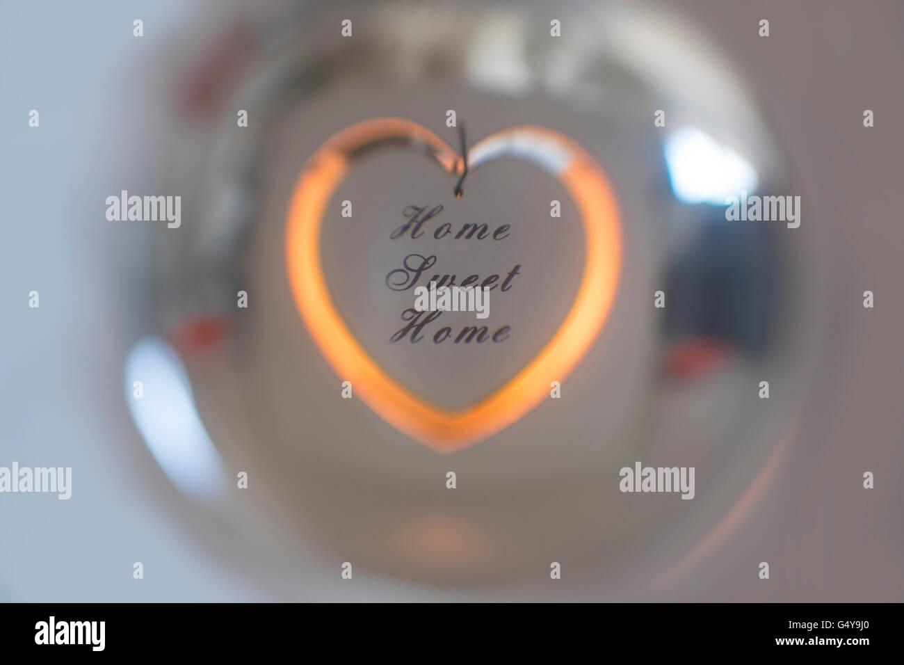 Home Sweet Home candle holder reflected in a crystal ball - Stock Image