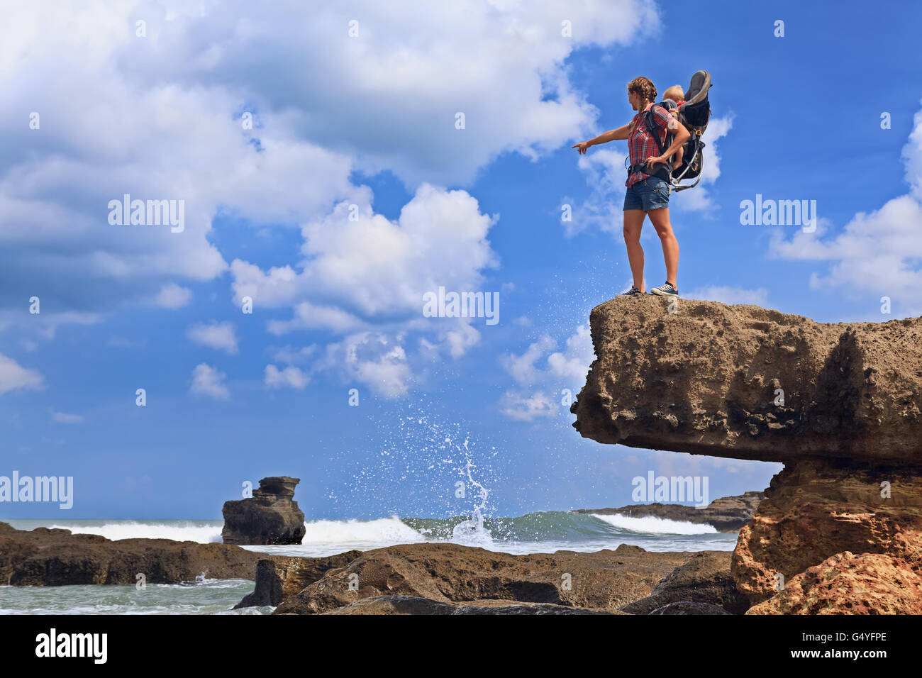 Nature walk on sea beach. Happy mother high rock cliff hold little traveller in carrying backpack. Baby ride on - Stock Image