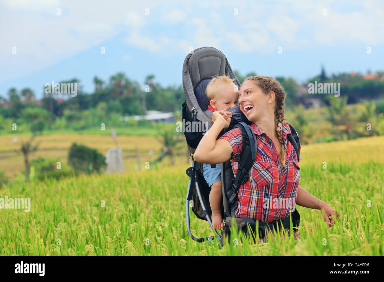 Nature walk in green rice terrace field. Happy mother hold little traveller in carrying backpack. Baby ride on woman - Stock Image
