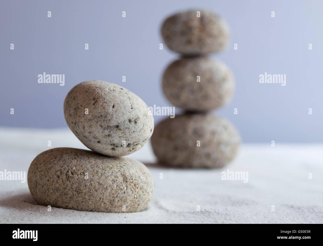Meditative stones in balance on white sand - Stock Image