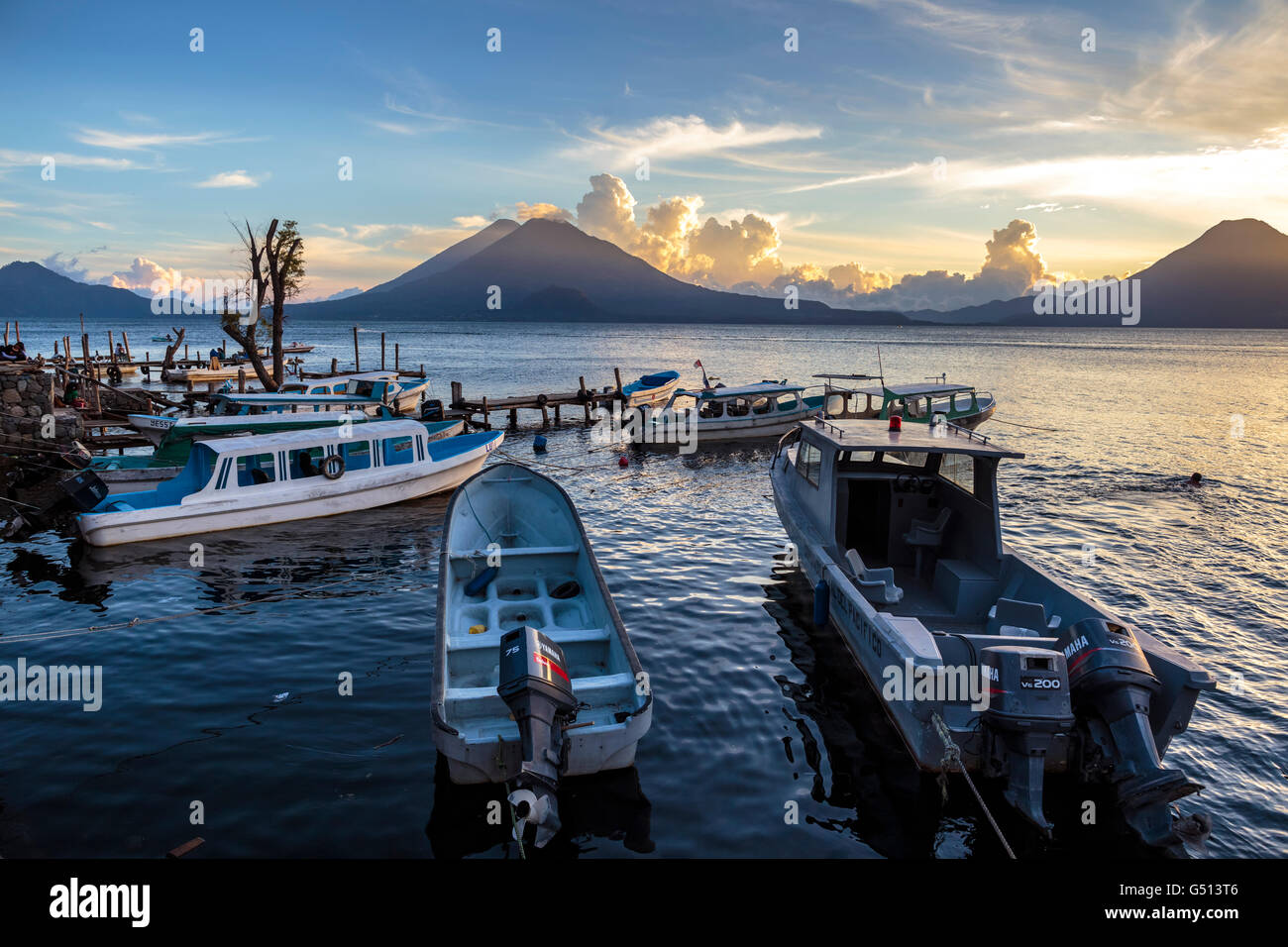 Sunset over the volcanoes of Lago de Atitlan in Guatemala and water taxis sit moored at the docks of the tourist - Stock Image