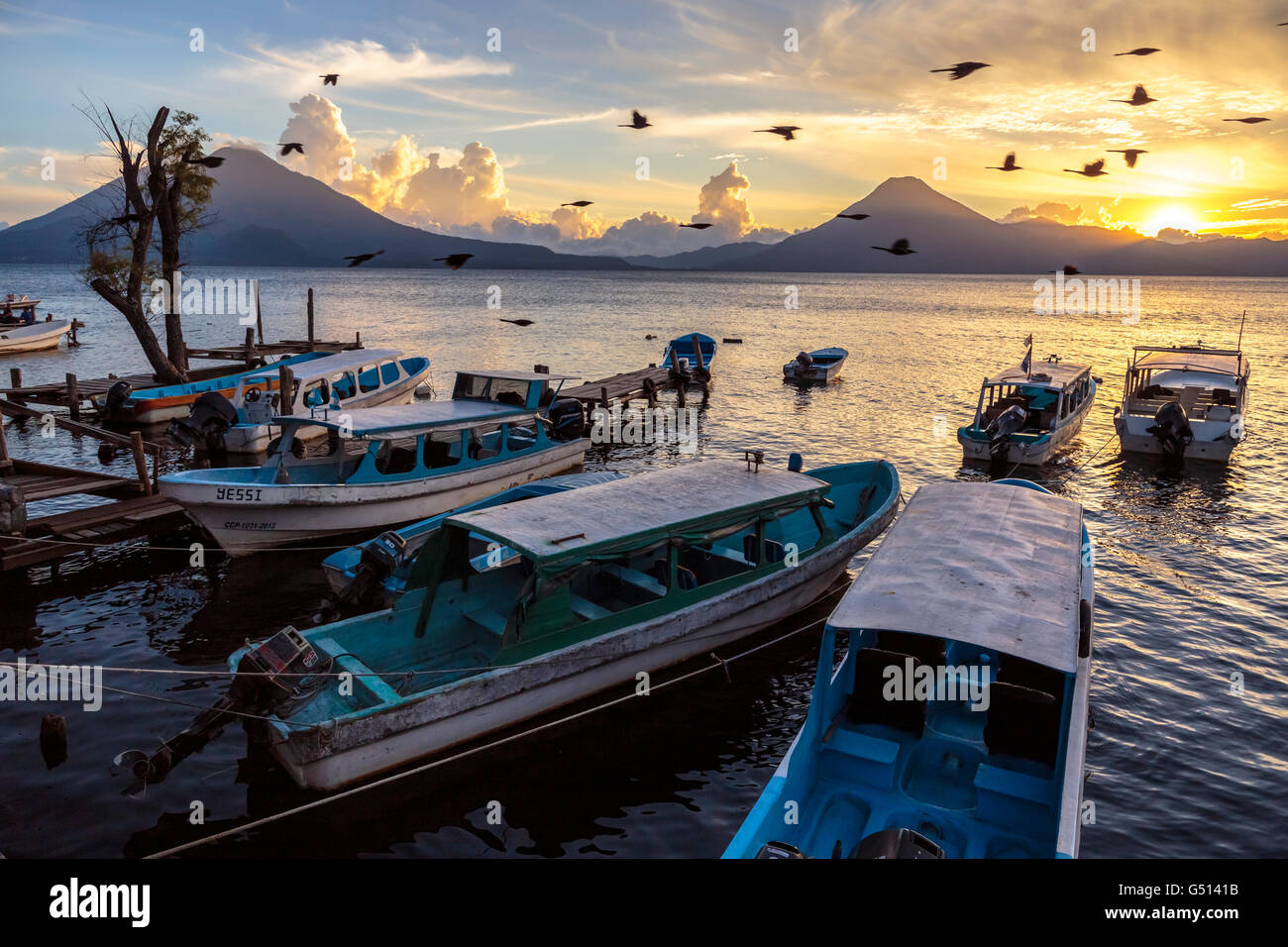 Birds fly by moored Water Taxis at the docks in Panajachel as the sun sets over the Volcanoes of Lago de Atitlan - Stock Image