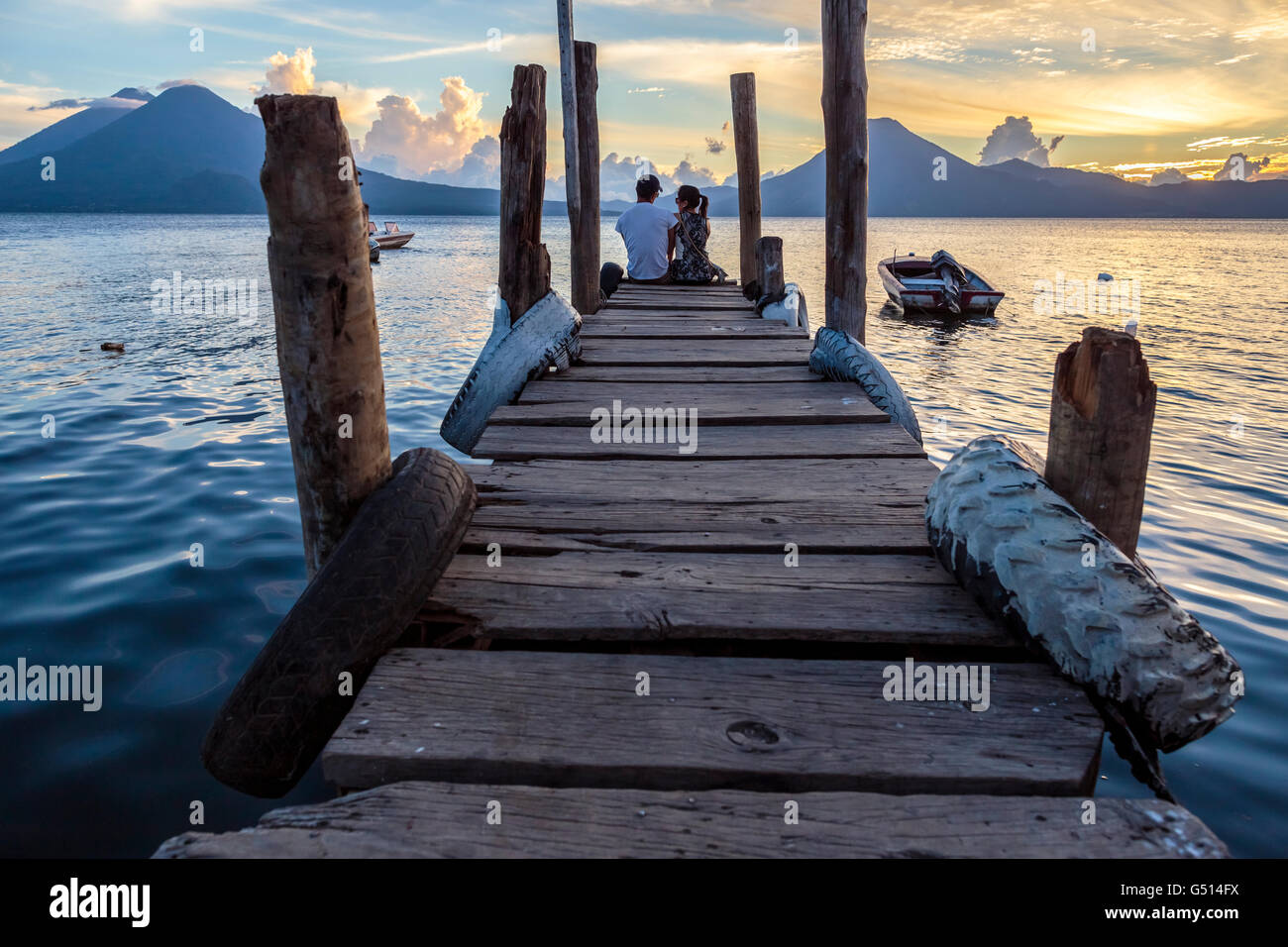 A couple of tourists sit on the dock in Panajachel as the sun sets over Lago de Atitlan, a volcanic crater lake - Stock Image