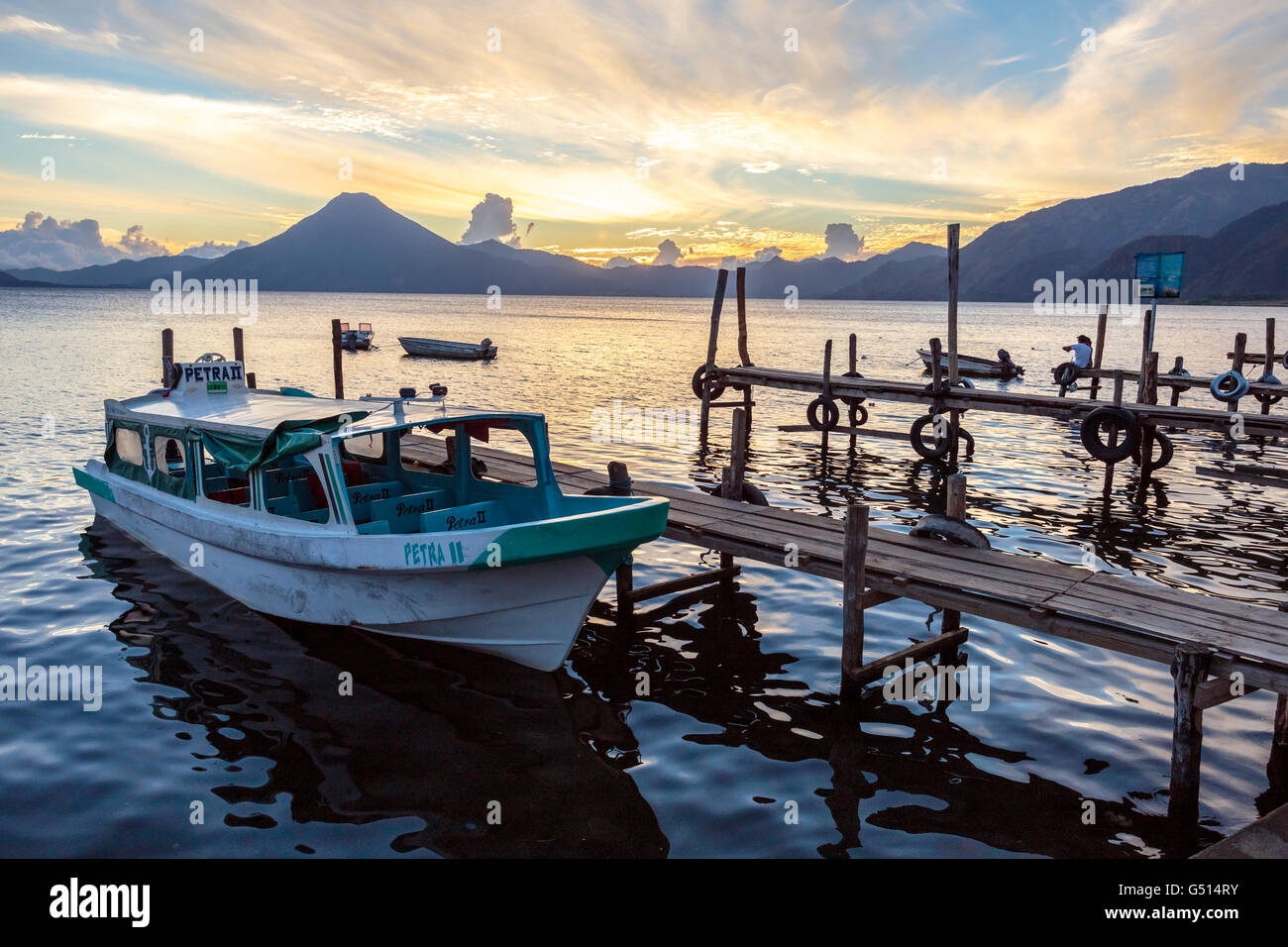 A water taxi sits docked in Panajachel for the evening as the sun sets over Lago de Atitlan, a volcanic crater lake - Stock Image