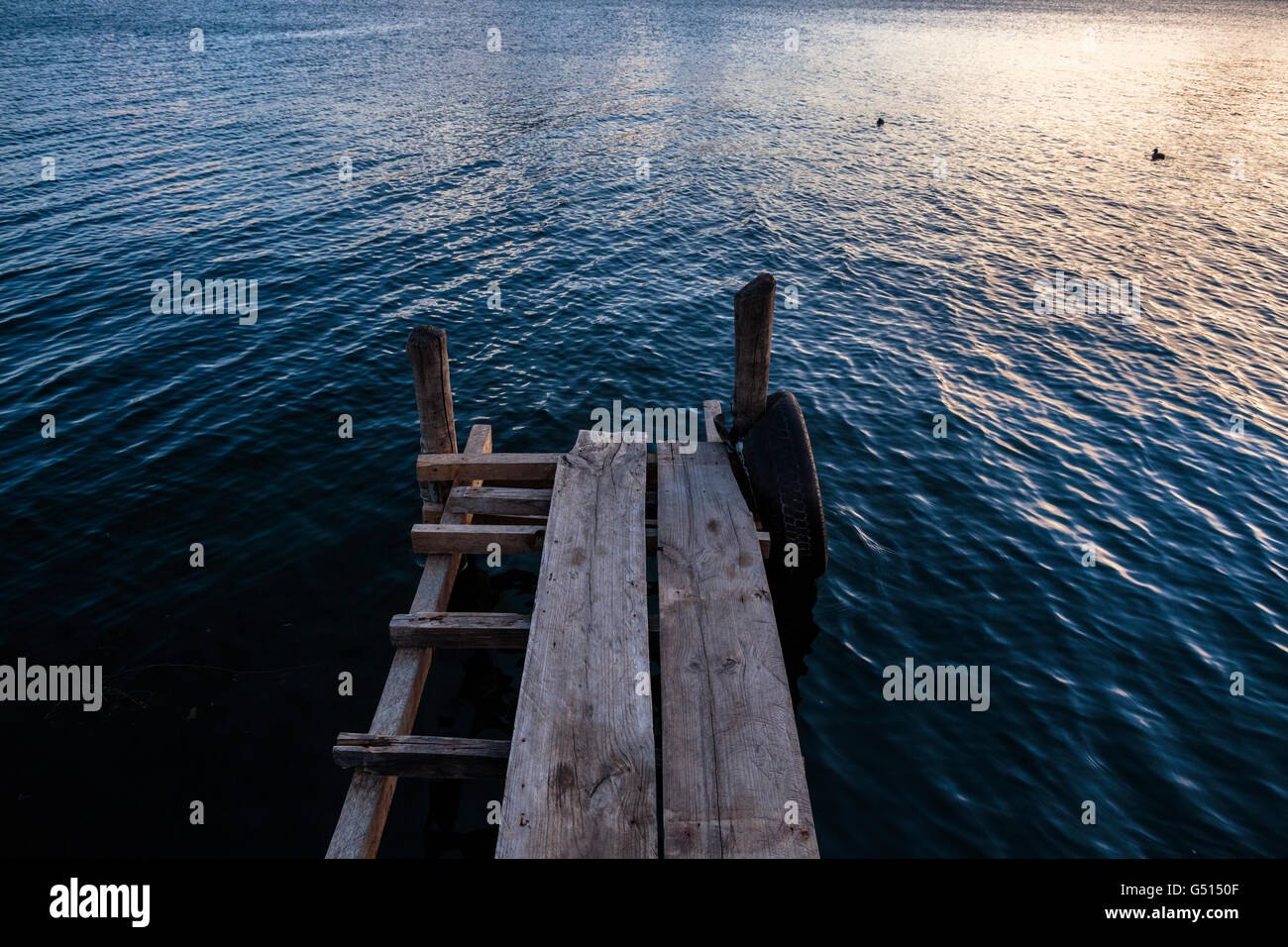 The sun sets over Lago de Atitlan in Guatemala, and birds fly past a rickety dock in Panajachel, a tourist hub for - Stock Image