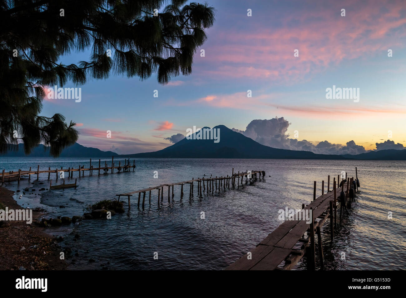 The sunset paints the sky over the outline of San Pedro Volcano across Lago de Atitlan in Guatemala at the docks - Stock Image
