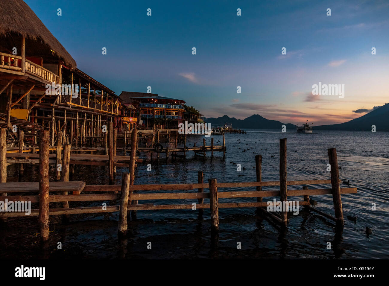 The sun sets over Lago de Atitlan in Guatemala, and tourists and locals gather by the docks in Panajachel as the - Stock Image