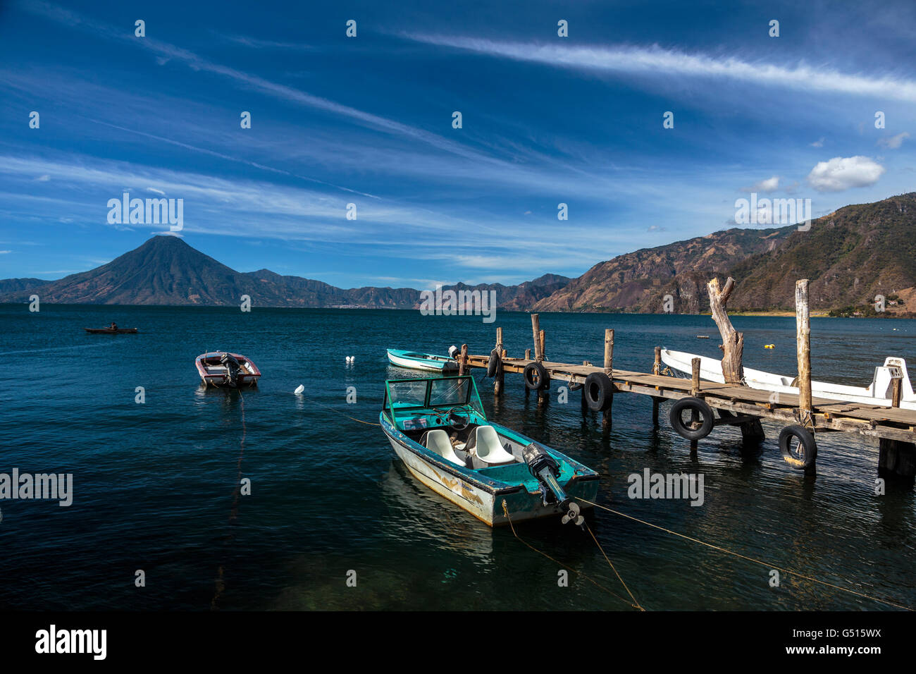 Blue skies over Lago de Atitlan and San Pedro Volcano, Guatemala where boats are moored at the docks on the lakeshore - Stock Image
