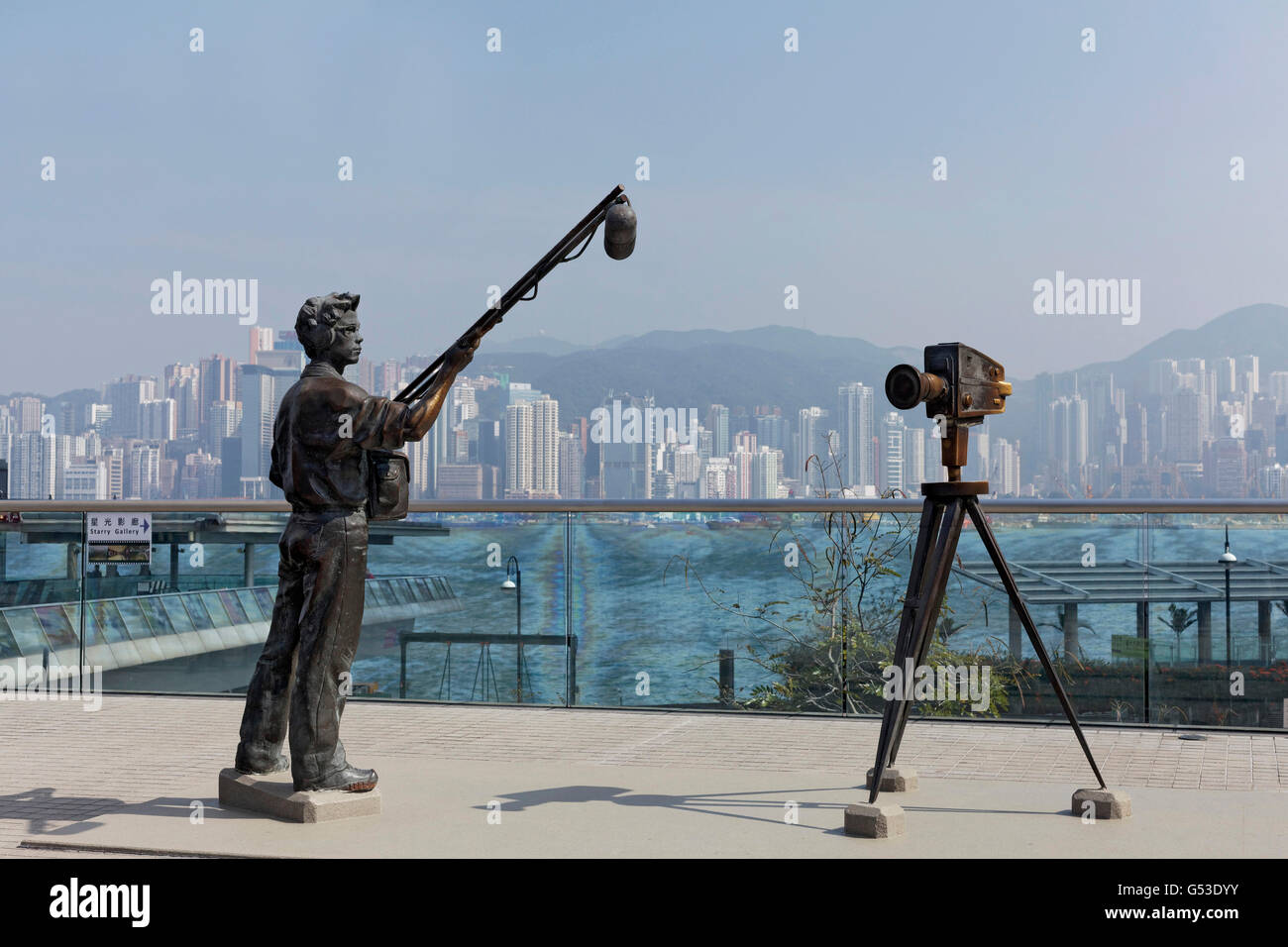 Sound assistant and film camera, bronze sculptures, Avenue of Stars with view of Hong Kong Island, Tsim Sha Tsui, - Stock Image