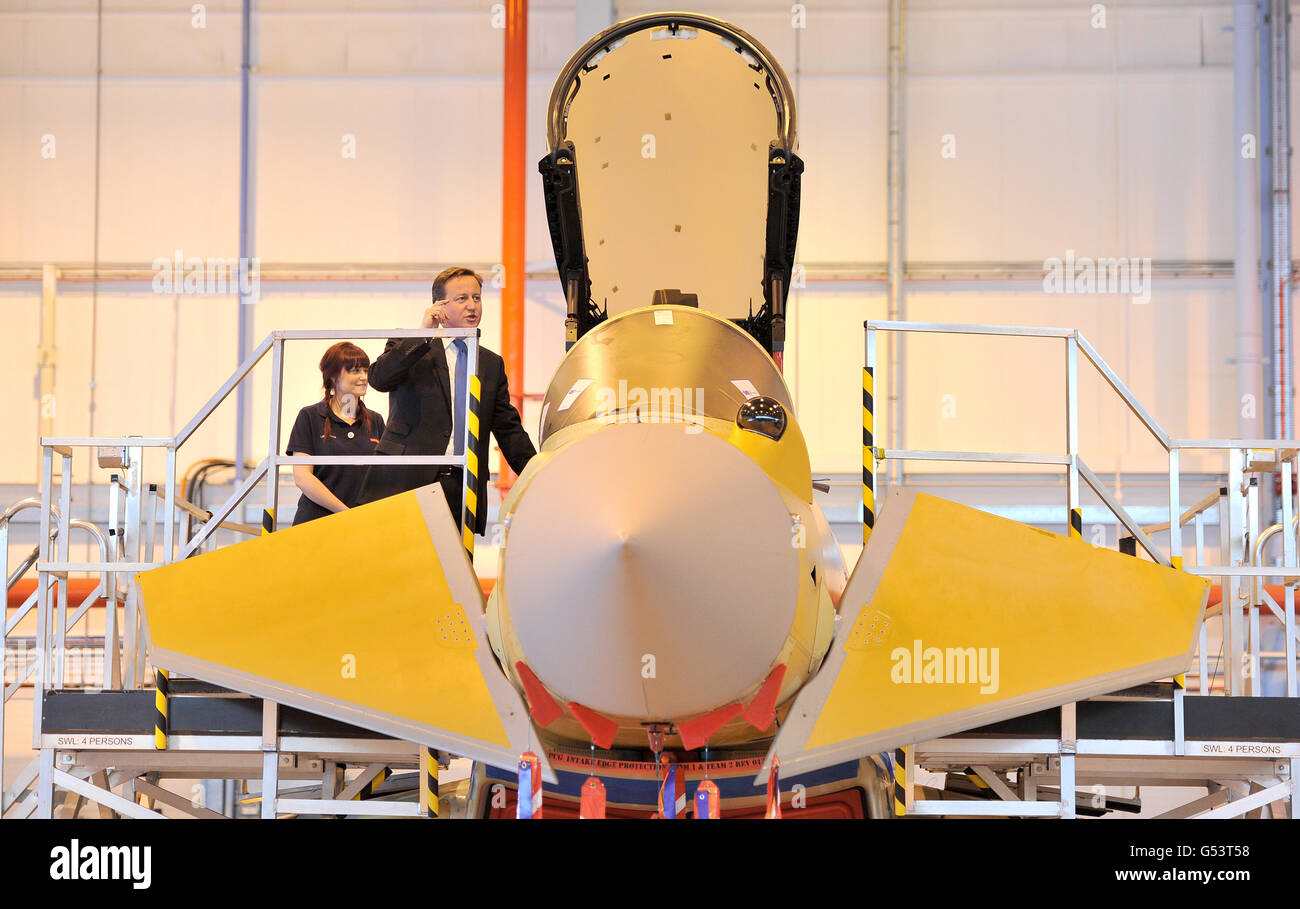 Prime Minister David Cameron views the Eurofighter Typhoon with apprentice Lauren Nuttall (left) during a visit to BAE Systems in Warton, Lancashire. Stock Photo