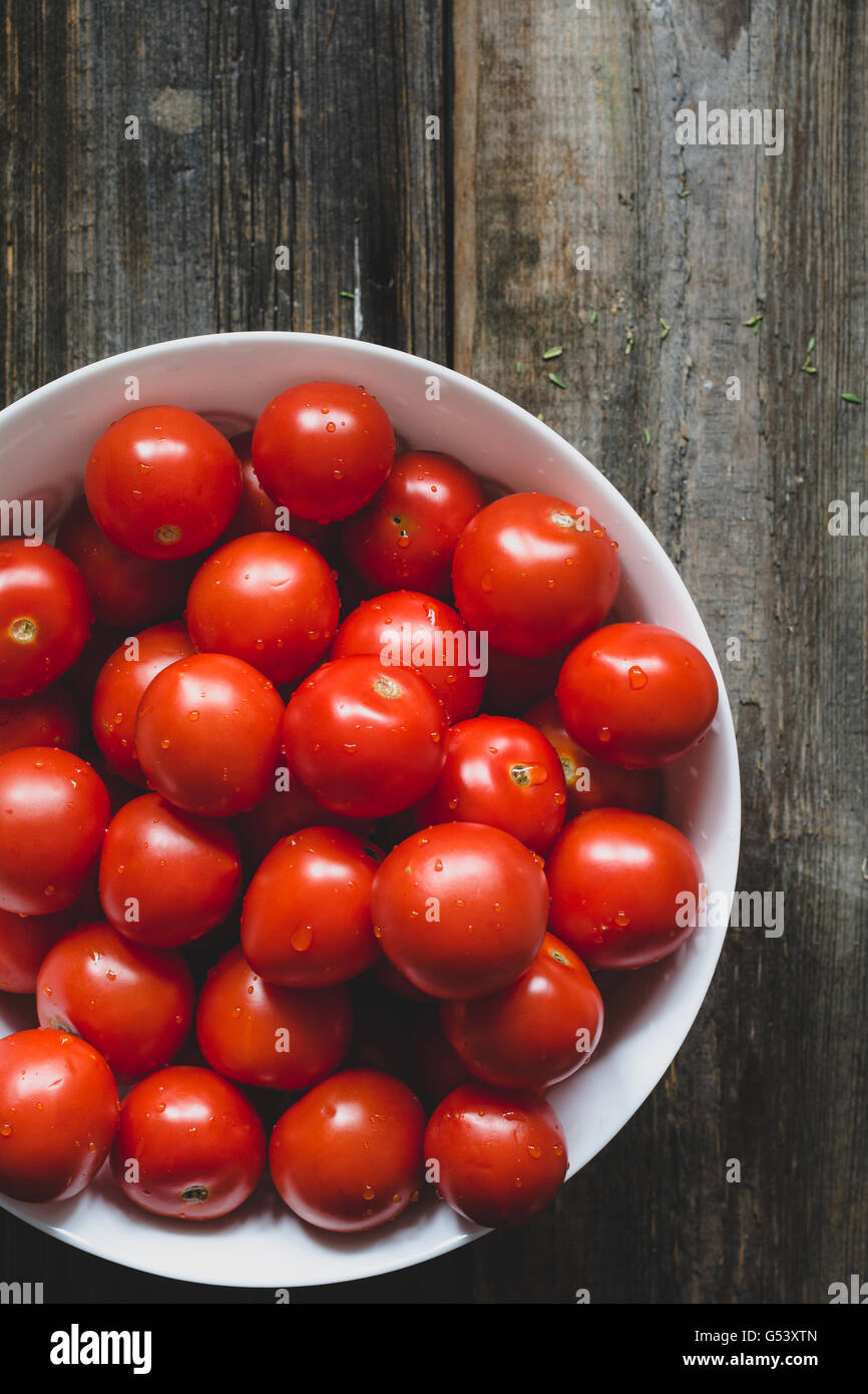 Cherry tomatoes covered with water drops in white bowl on rustic wooden backdrop. Top view, selective focus, toned - Stock Image