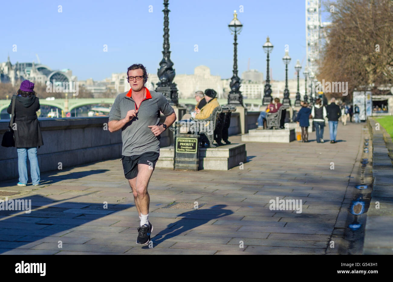 Man jogging on the south bank of the River Thames in Lambeth, London, England, UK. - Stock Image