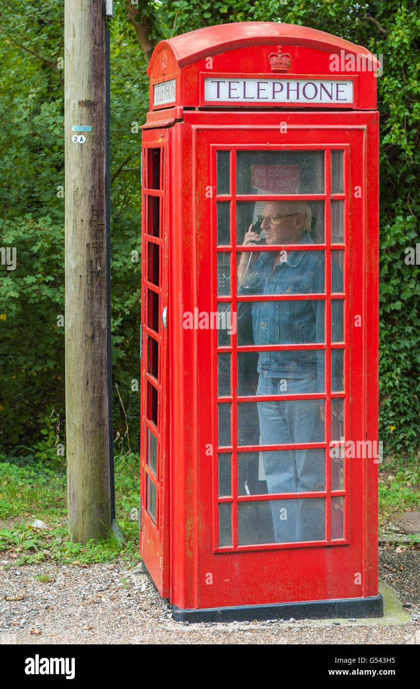 Man using an old style British red telephone box. - Stock Image