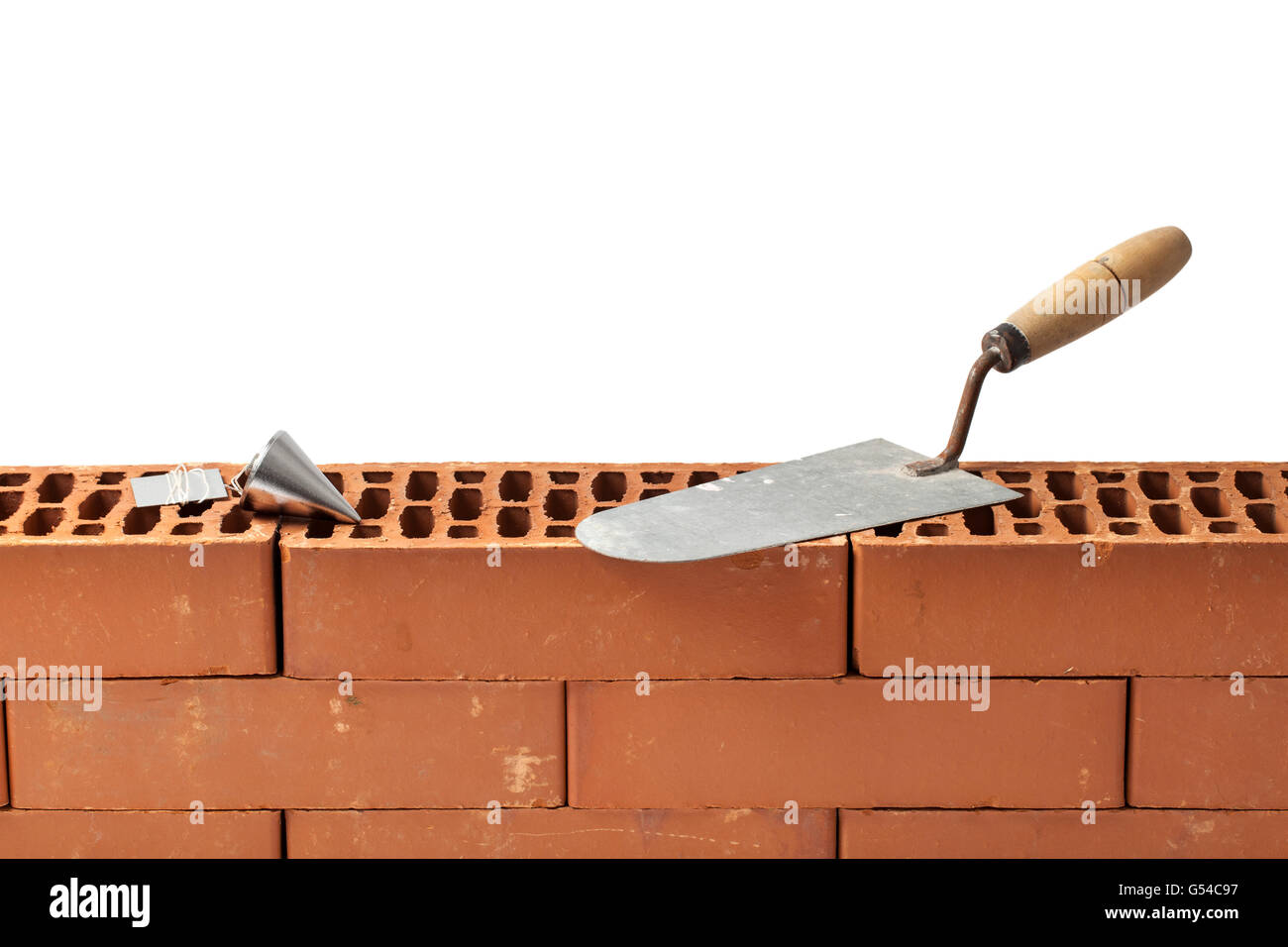 Construction tools trowel and plumb bob left on a new brickwork isolated on white. Stock Photo
