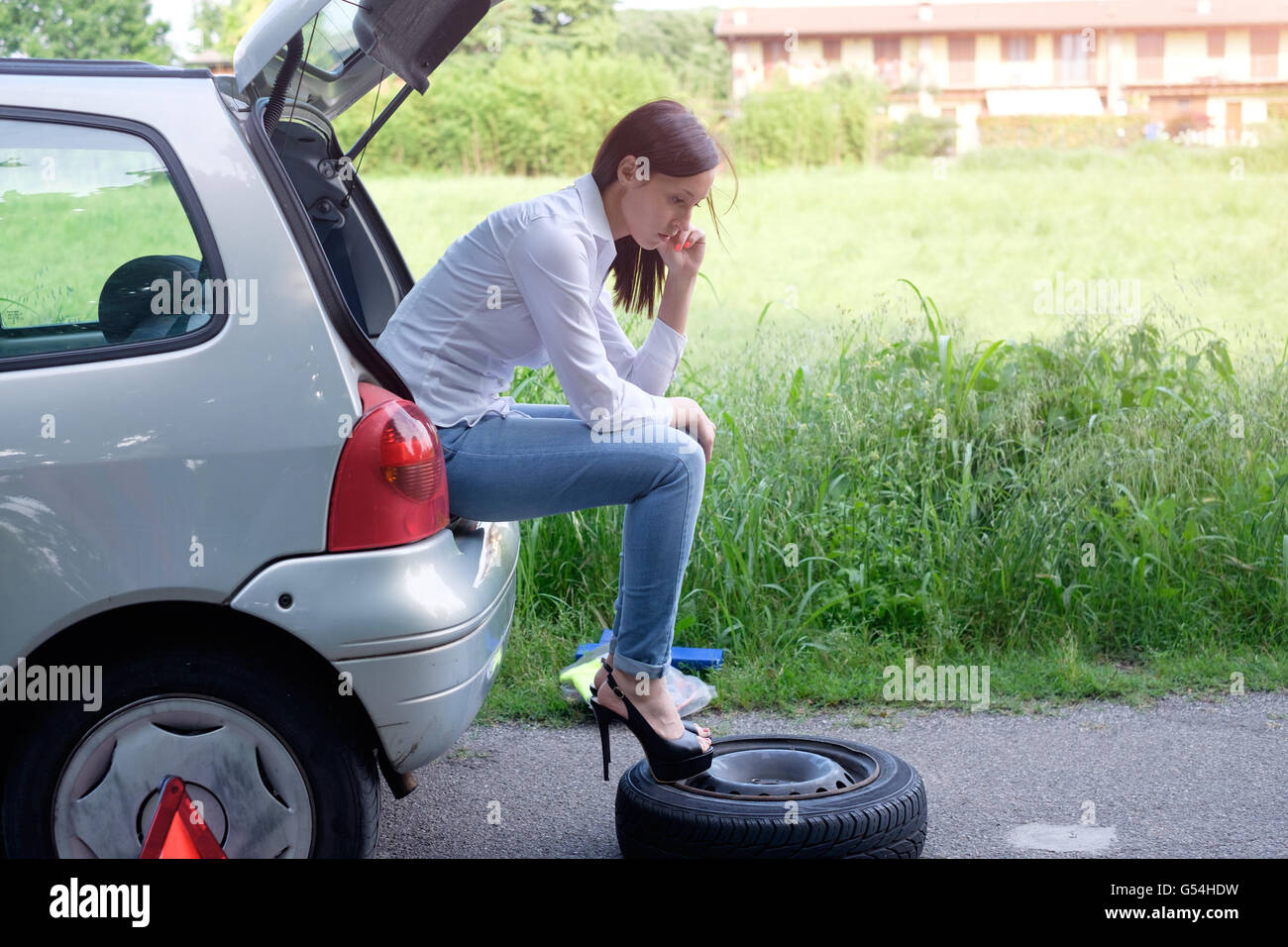 Sad woman calling assistance service  after unexpected vehicle breakdown - Stock Image