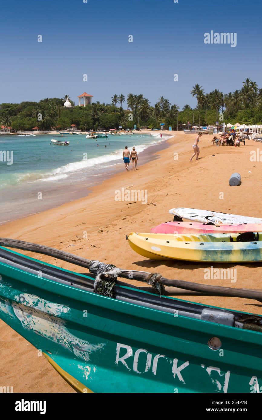 Sri Lanka, Galle Province, Unawatuna, tourists walking on, artificial imported sand beach Stock Photo