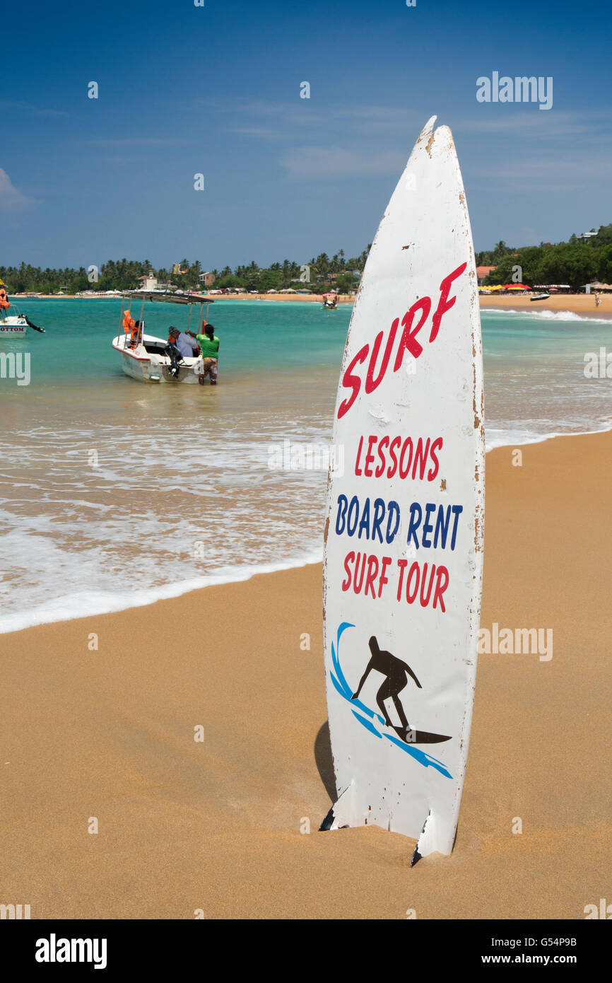 Sri Lanka, Galle Province, Unawatuna beach, surf school sign on surfboard - Stock Image