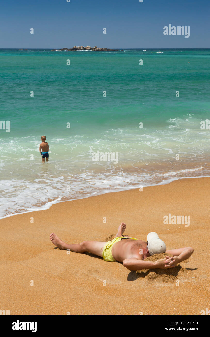 Sri Lanka, Galle Province, Unawatuna beach, sunbather on sand and young boy in shallows Stock Photo