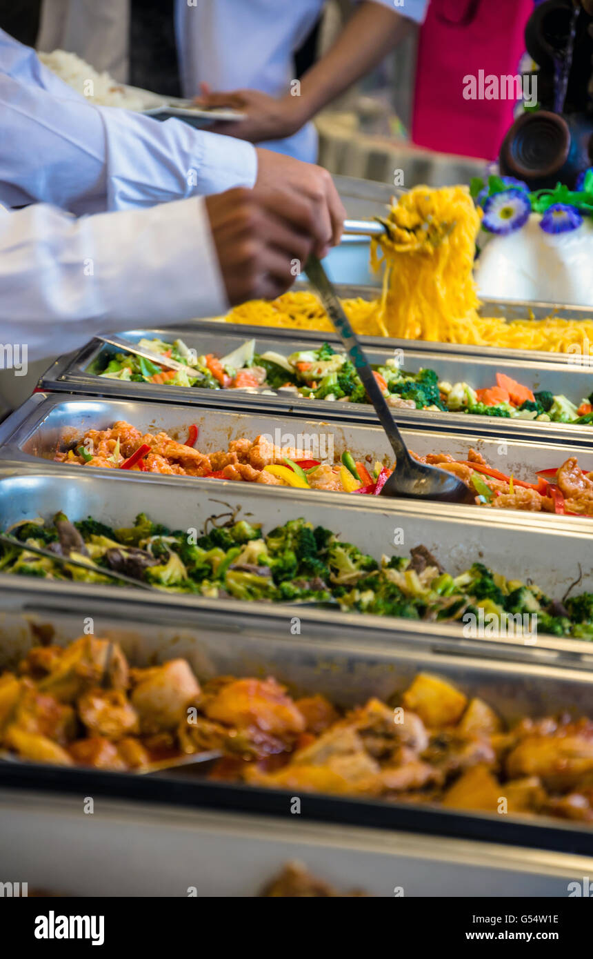 People help themselves to food at a self-service buffet at a party. - Stock Image