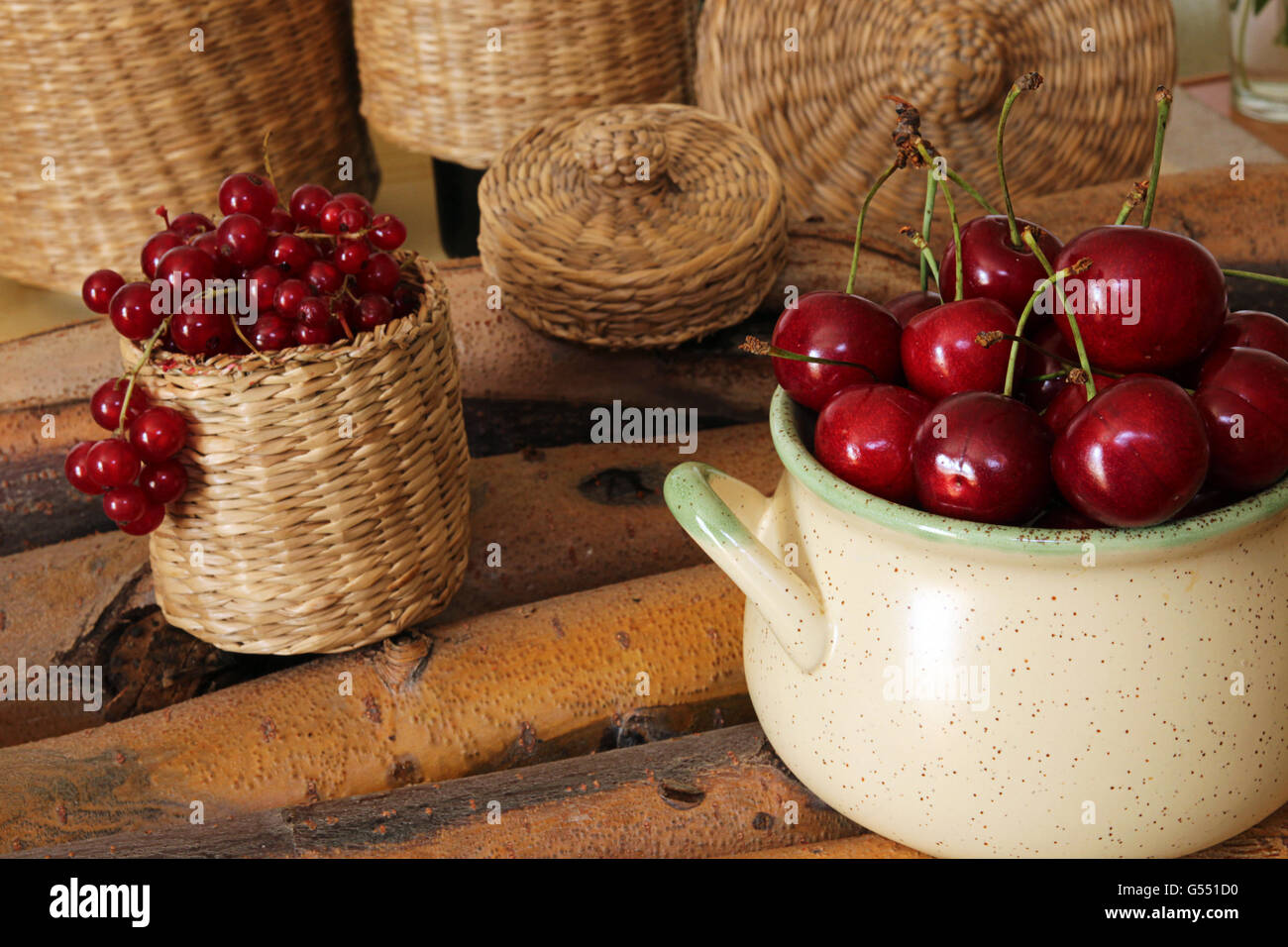 Sweet cherry in ceramic bowl and red currant in wattled bast basket - Stock Image