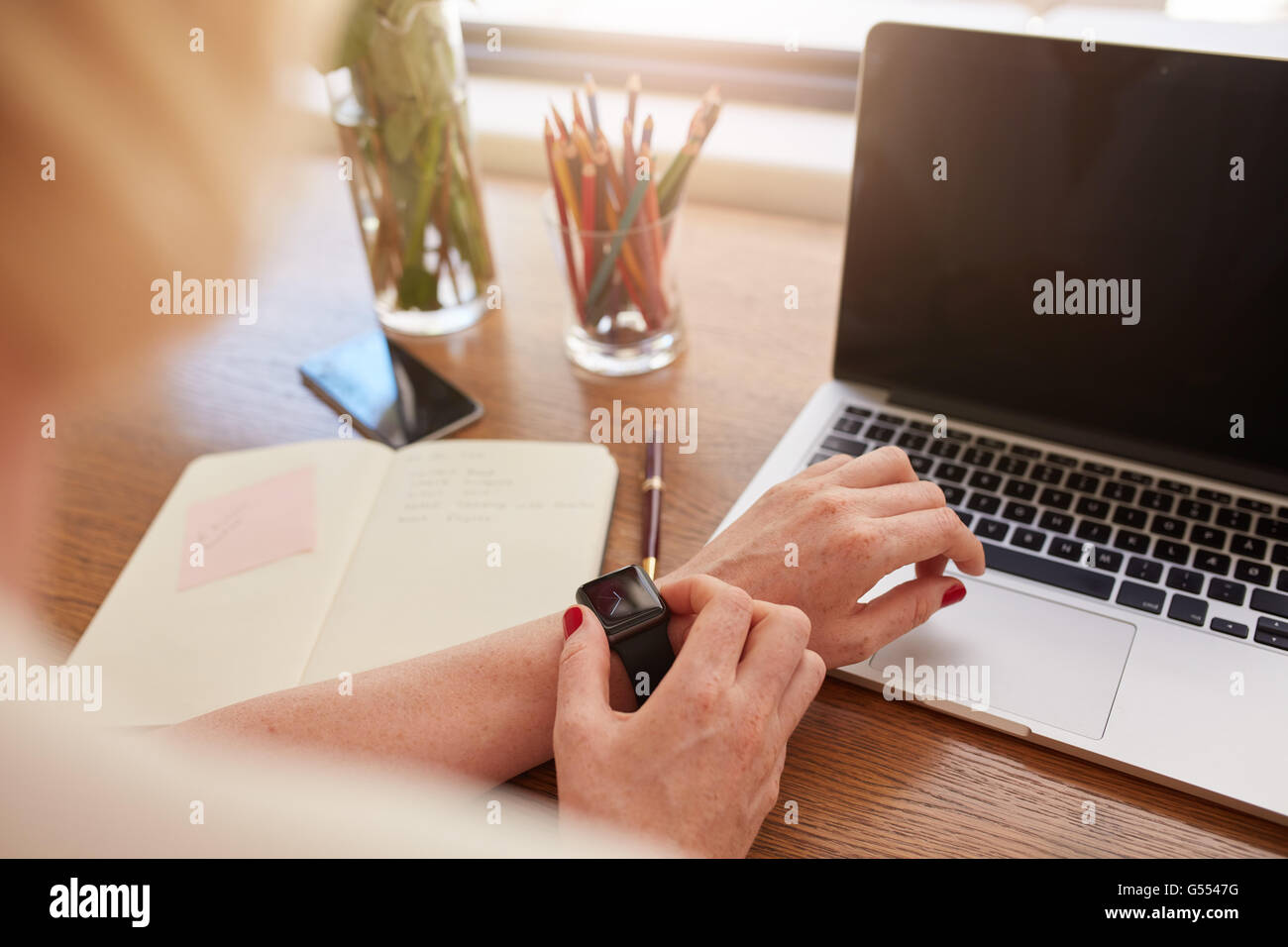 Close up shot of woman using smartwatch. Focus on female hands and smart watch with laptop and diary on table. Stock Photo