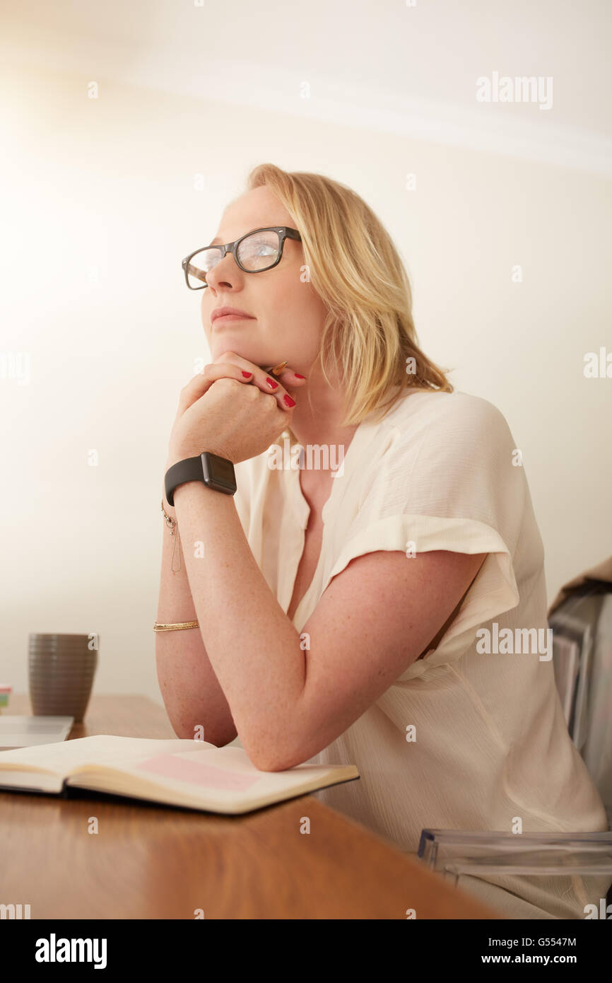 Portrait of mature businesswoman sitting at her desk and looking away thinking. Caucasian female sitting in her - Stock Image