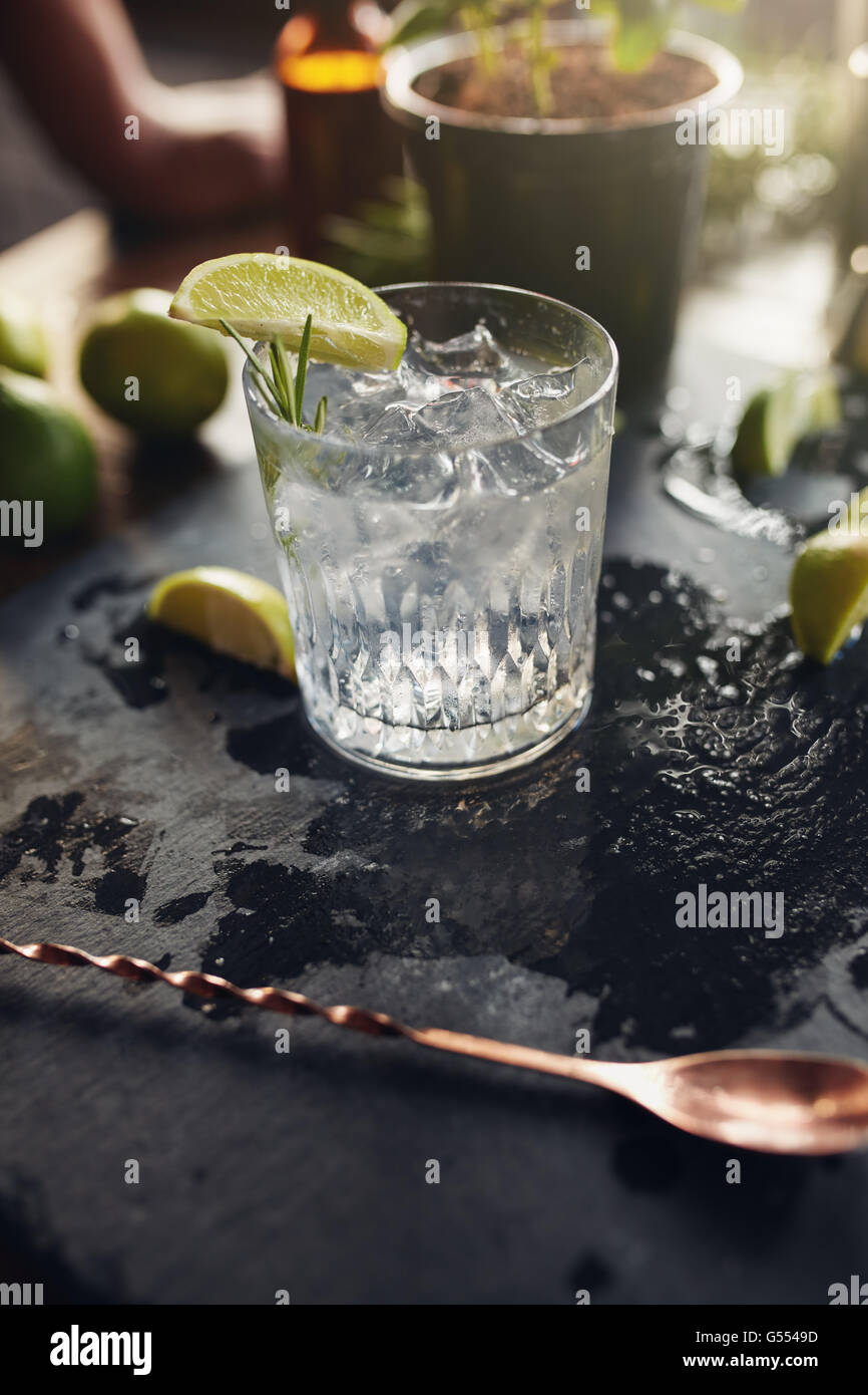 Glass of fresh cocktail drink with lemon slice and ice cubes on a black board. - Stock Image
