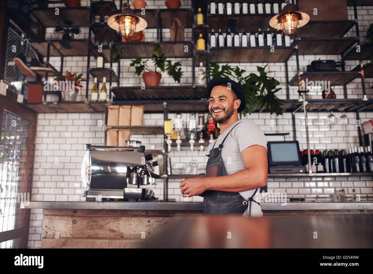 Indoor shot of happy young bar owner standing at the counter and looking away smiling - Stock Image